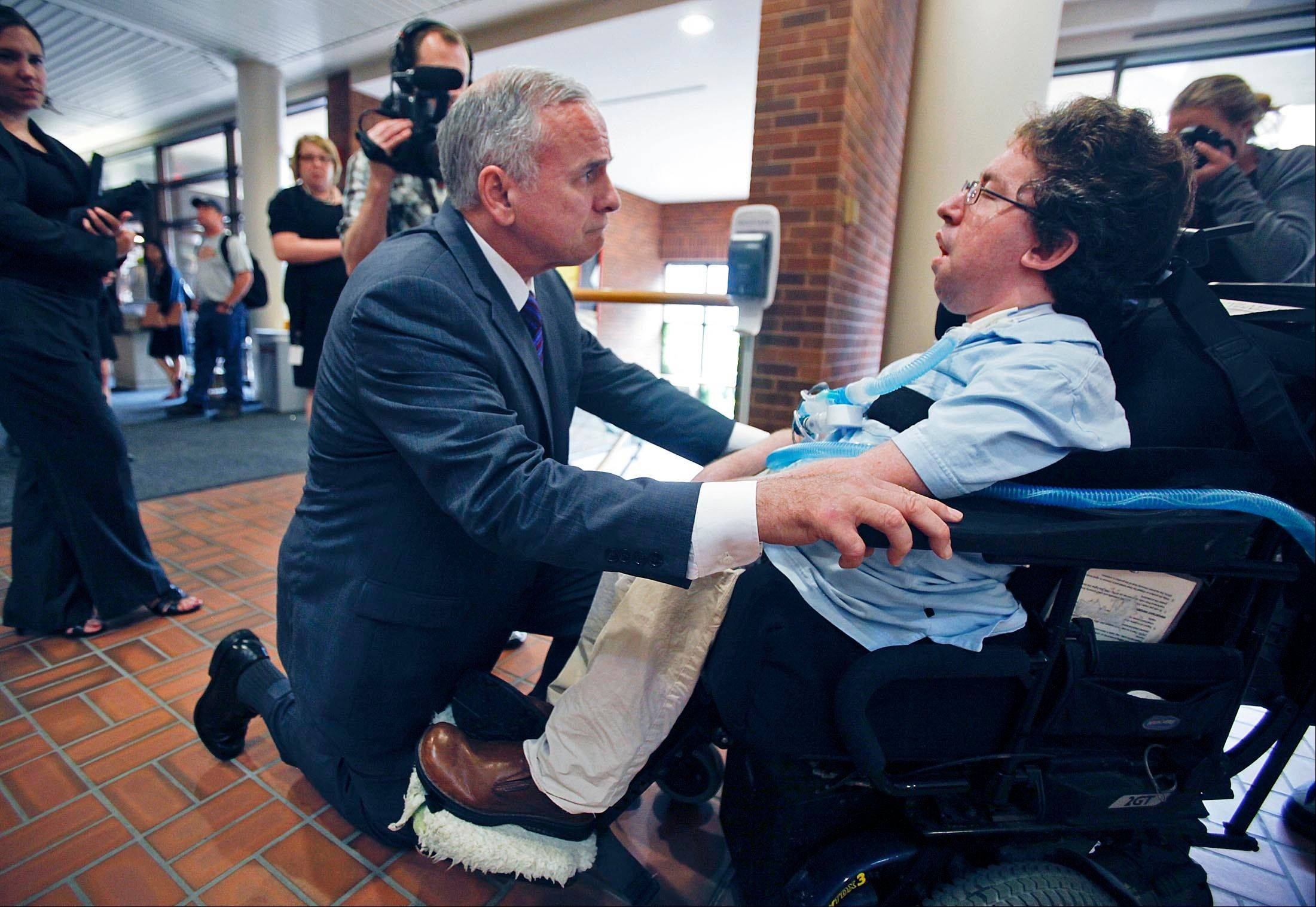 Minnesota Gov. Mark Dayton gets down on a knee to talk to Mark Siegel, a state employee and blogger, after Dayton appeared at the University of Minnesota's Hubert H. Humphrey School Thursday and announced he would seek a budget deal with GOP leaders.
