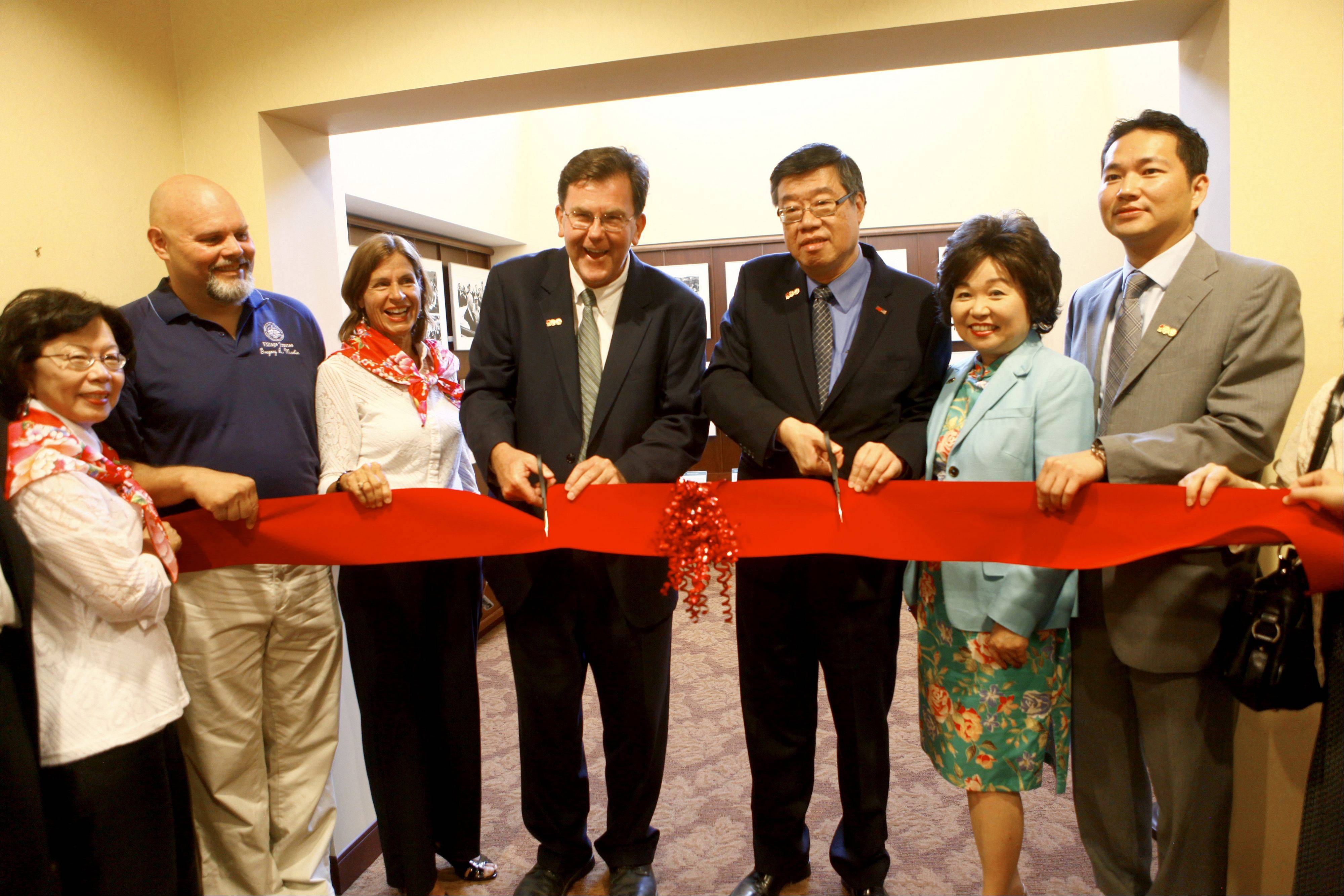 Bartlett Village President Michael E. Kelly, middle left, and Perry Shen, director general of the Taipei Economic Cultural Office in Chicago, cut the ribbon to open the photo exhibit Thursday at the village hall. The exhibit is on display until July 26.