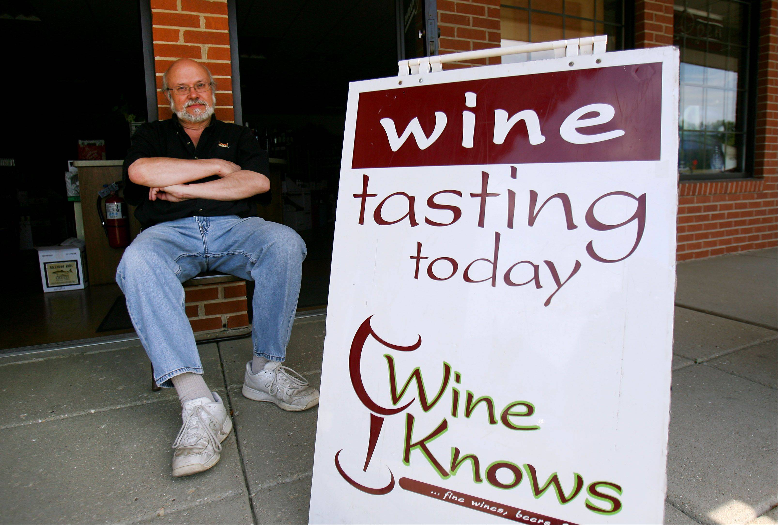 Phil Grenier, owner of Wine Knows in Grayslake, sits outside his business as he tries to attract customers for a wine tasting Thursday. It was the fourth day Grenier's store was without power.