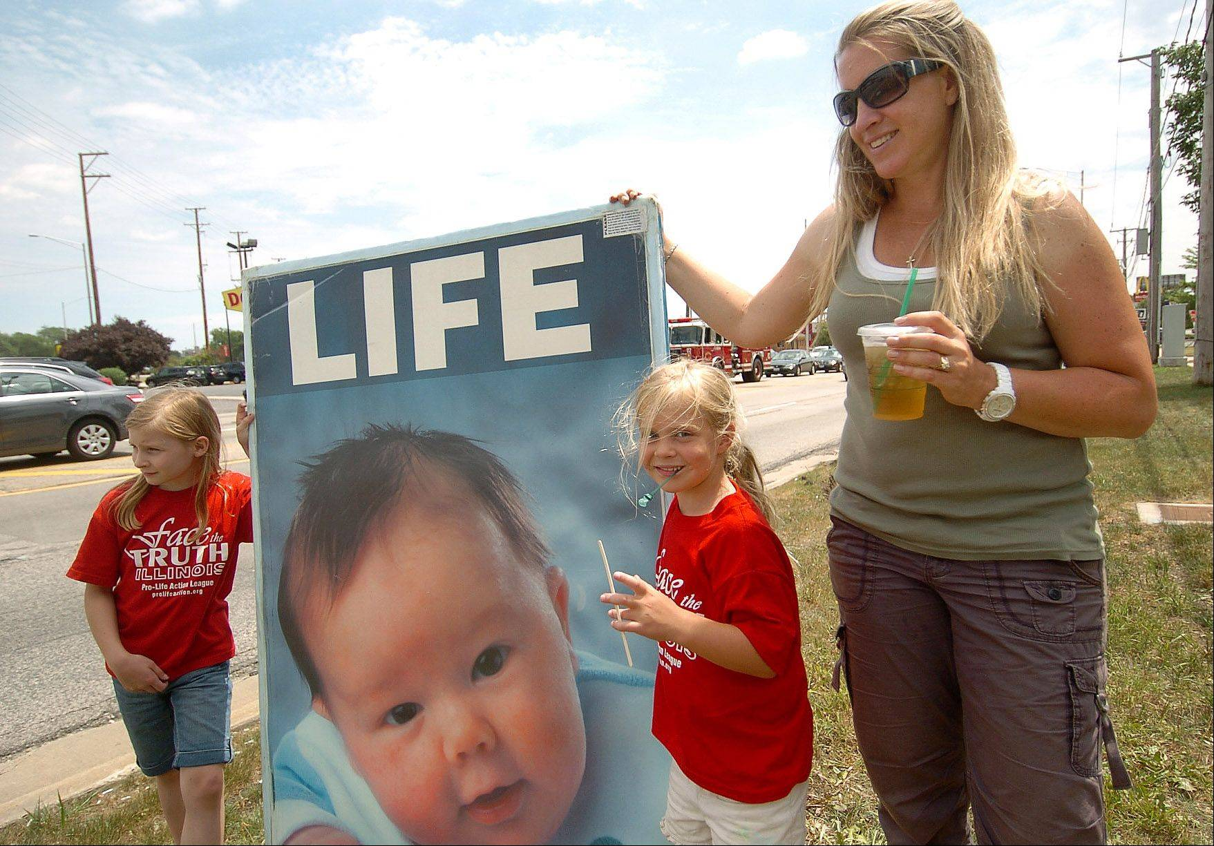 From left, Ada Scheidler, Hope Miller and mom Cathy Miller of Lake Zurich take part in the Pro-Life Action League's anti-abortion demonstration today along Rand and Dundee roads in Palatine.