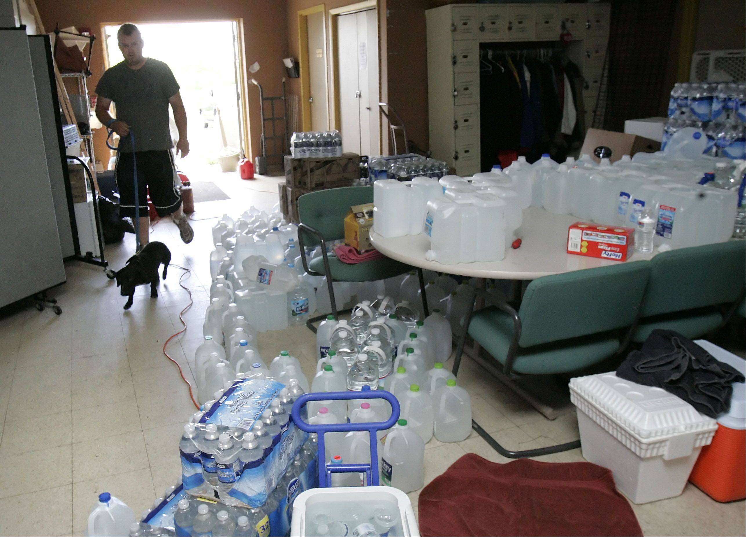 "Save-A-Pet staff member Teig Evans walks ""Bubba"" past donated bottles of water Wednesday as the facility continues to cope without power."