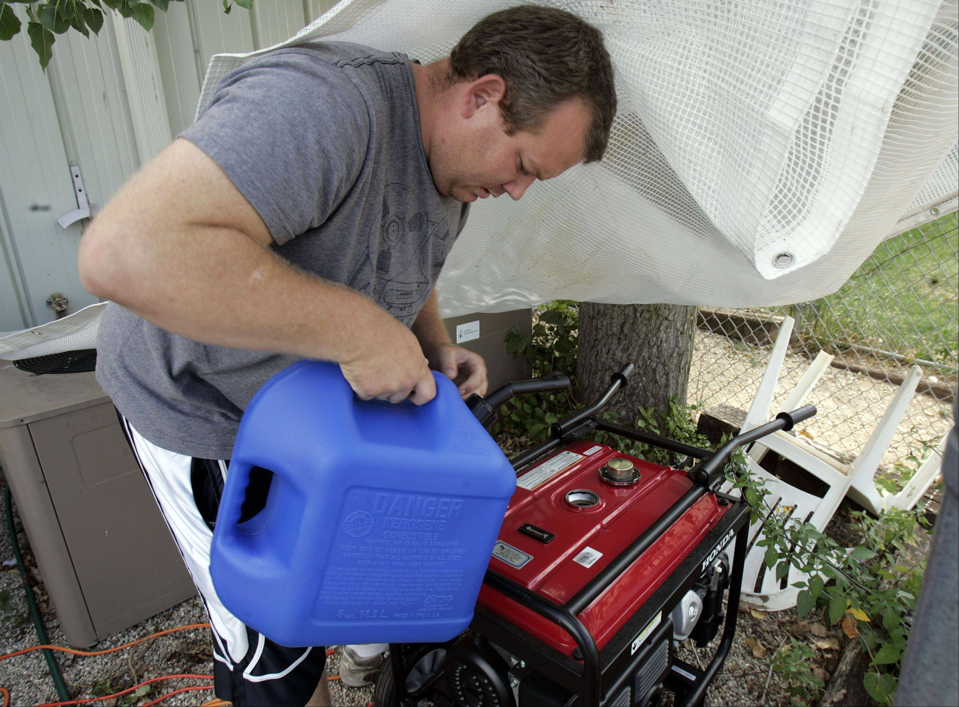 Save-A-Pet staff member Teig Evans fills a generator with gasoline Wednesday at the Grayslake shelter. Portable generators provide enough power for fans and refrigerators as the facility remained without power.