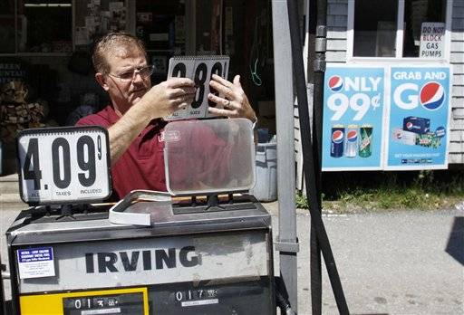 Convenience story owner Floyd Bisson, lowers the price of regular gas at the pumps in front of his store in Phippsburg, Maine.