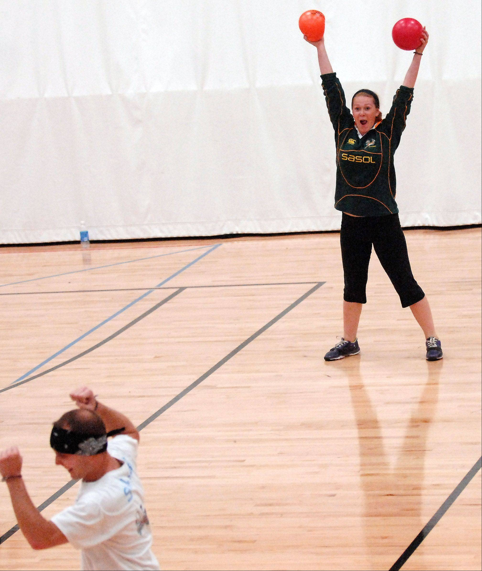 "Quin Gable, 19, of West Chicago throws her hands up in triumph after making a catch and putting someone out during a practice for the ""Hammertime"" dodgeball team at Christ Community Church in St. Charles Friday. They're preparing for this weekend's annual championship tournament of the National Amateur Dodgeball Association."