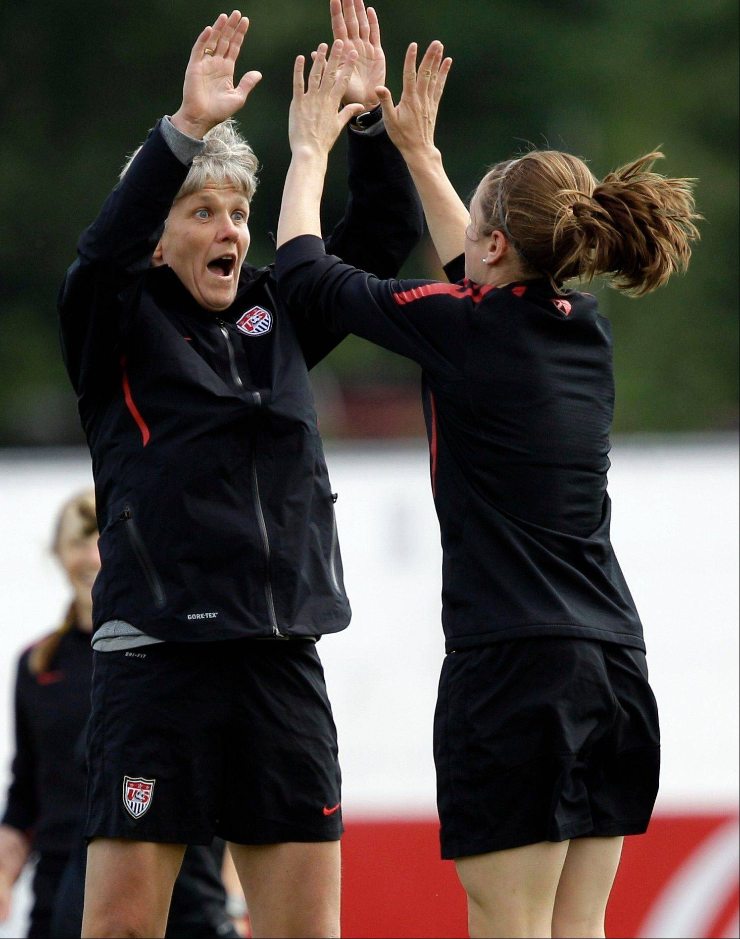 United States head coach Pia Sundhage, left, high fives midfielder Heather O'Reilly Friday during a training session in preparation for the final match against Japan during the Women's Soccer World Cup in Frankfurt, Germany.