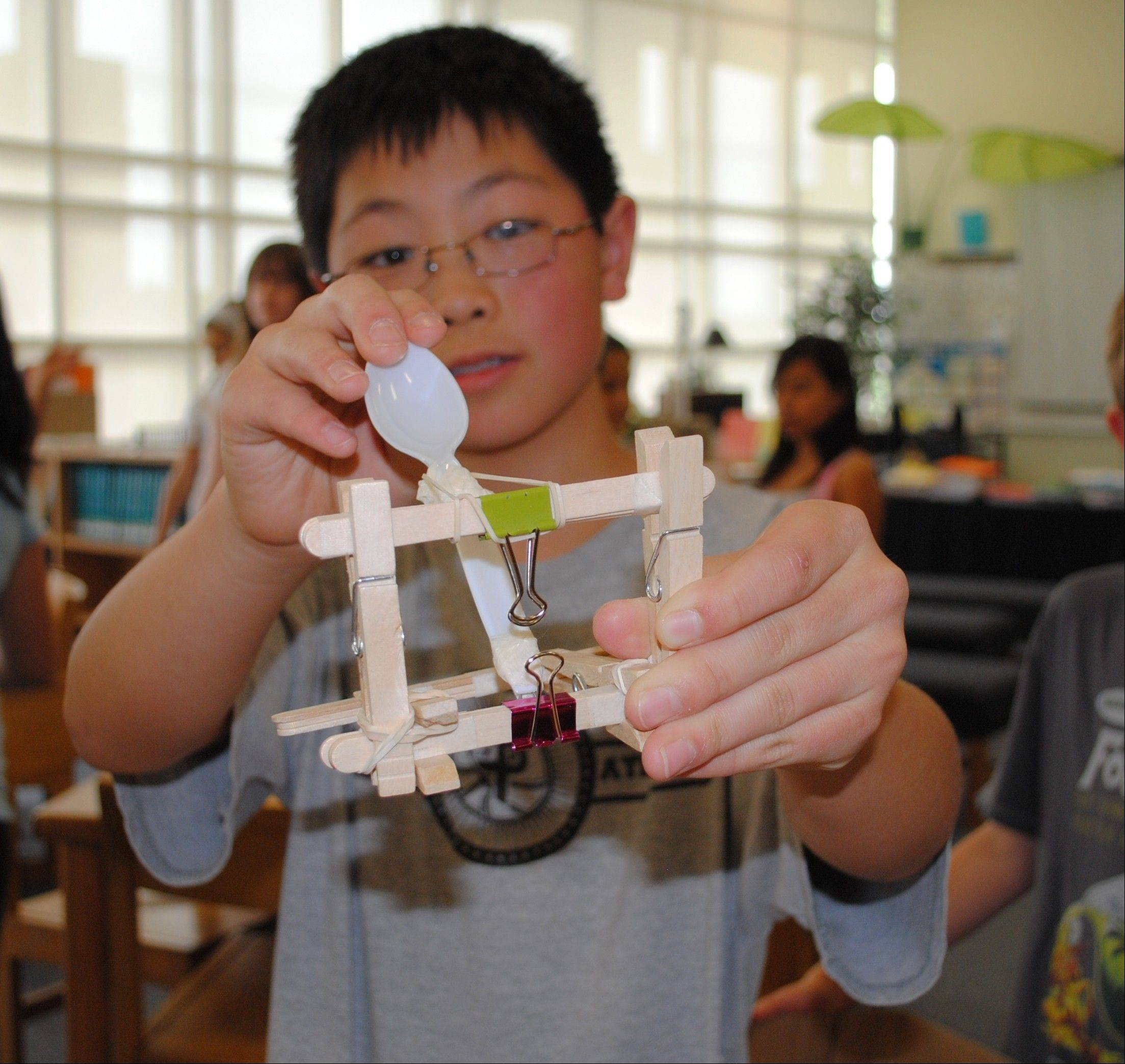 District 96 Country Meadows fifth-grader Daniel Hwang demonstrates the catapult he made to trade at the Country Meadows Trade Fair.