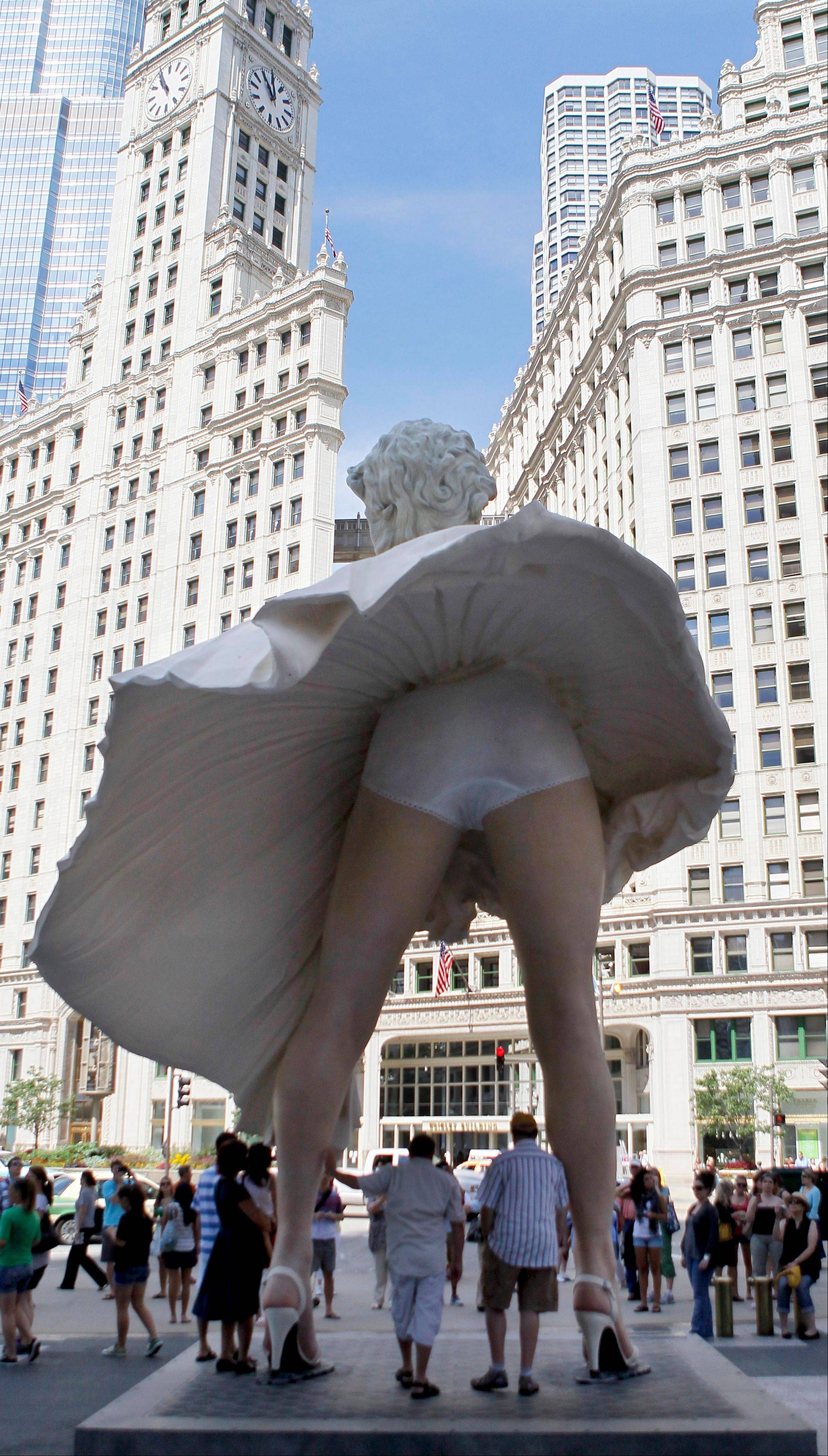 Curious spectators have their photo taken around Seward Johnson's 26-foot-tall sculpture of Marilyn Monroe, in her most famous windblown pose, on Michigan Ave. in Chicago.