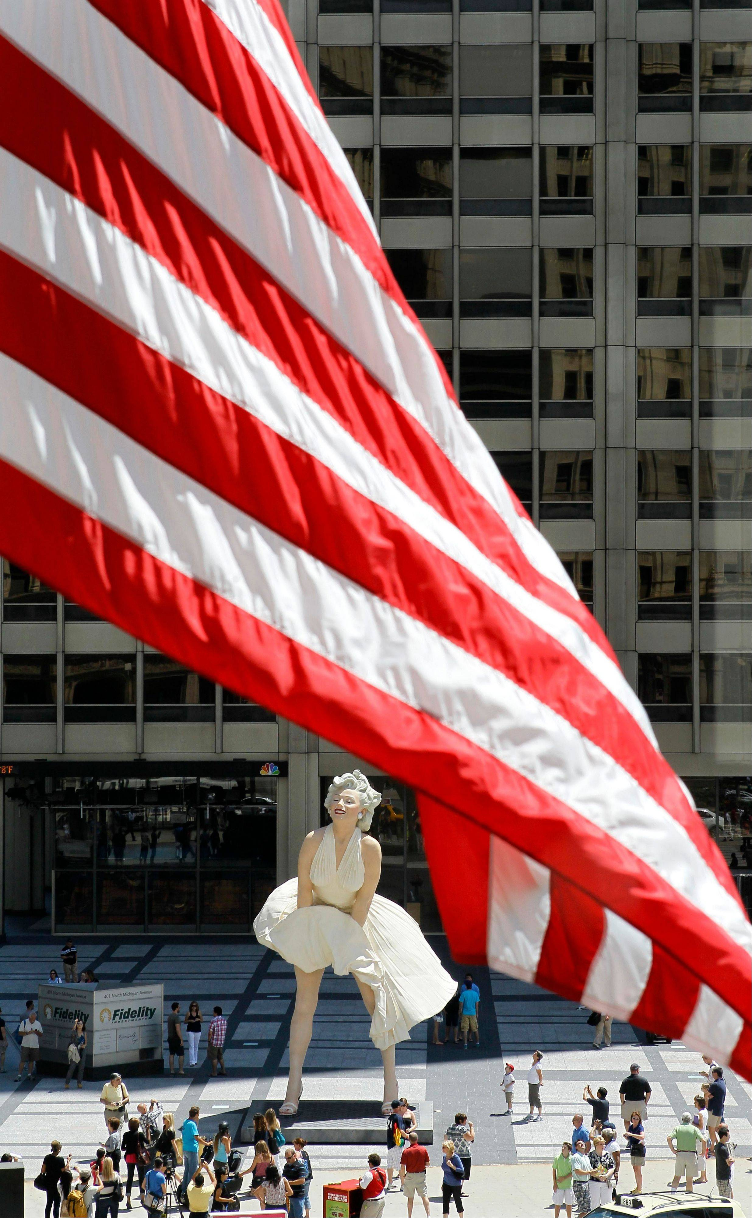 An American flag flying off the Wrigley Building is seen with Seward Johnson's 26-foot-tall sculpture of Marilyn Monroe, in her most famous windblown pose, across the street on Michigan Ave. in Chicago.