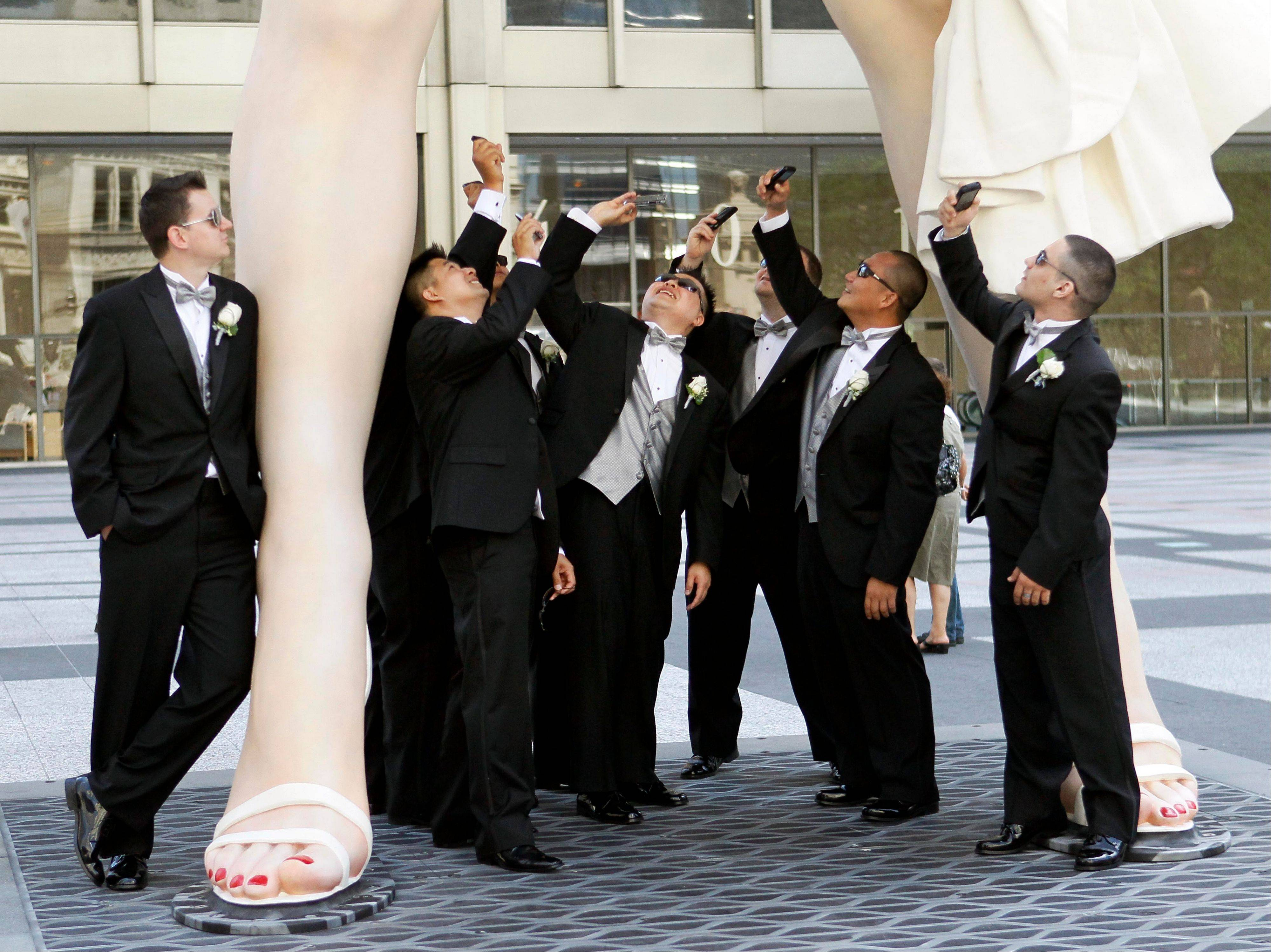 Members of the Hugh and Anya Nguyen wedding party pose under Seward Johnson's 26-foot-tall sculpture of Marilyn Monroe, in her most famous windblown pose, on Michigan Ave. in Chicago.