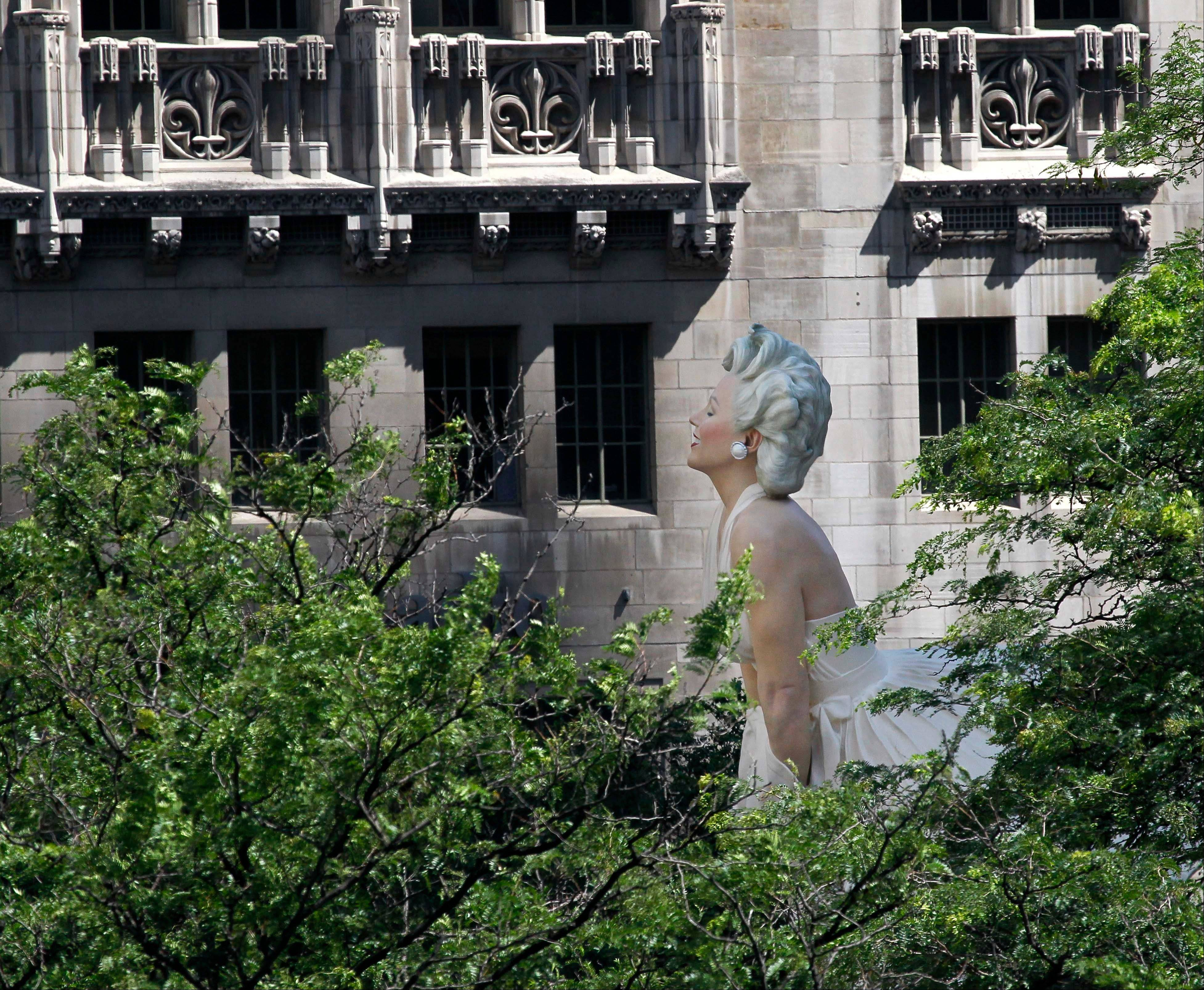 Seward Johnson's 26-foot-tall sculpture of Marilyn Monroe, in her most famous windblown pose, is seen across the Chicago River through trees on Michigan Ave. in Chicago.