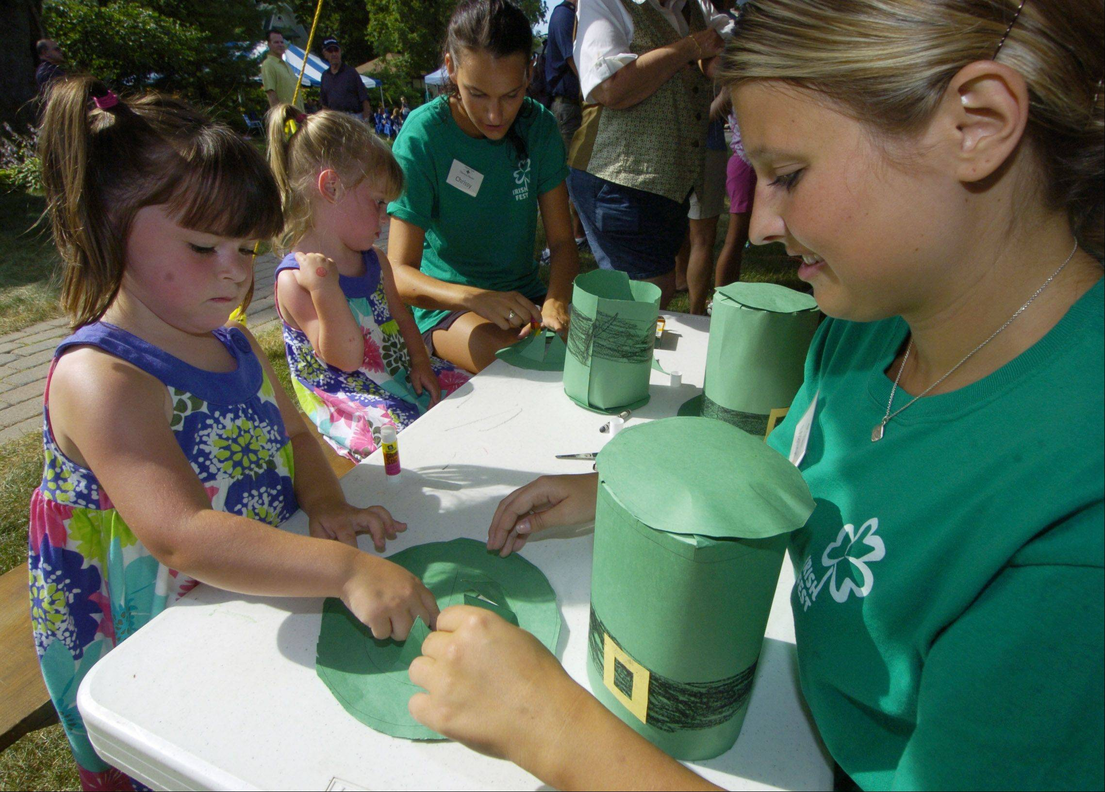 Shannon Kenney, age 4½, of Barrington, front, works on an paper Irish hat with park district intern Mallory Volocyk, while her twin sister, Samantha, works with intern Chrissy Tiske.