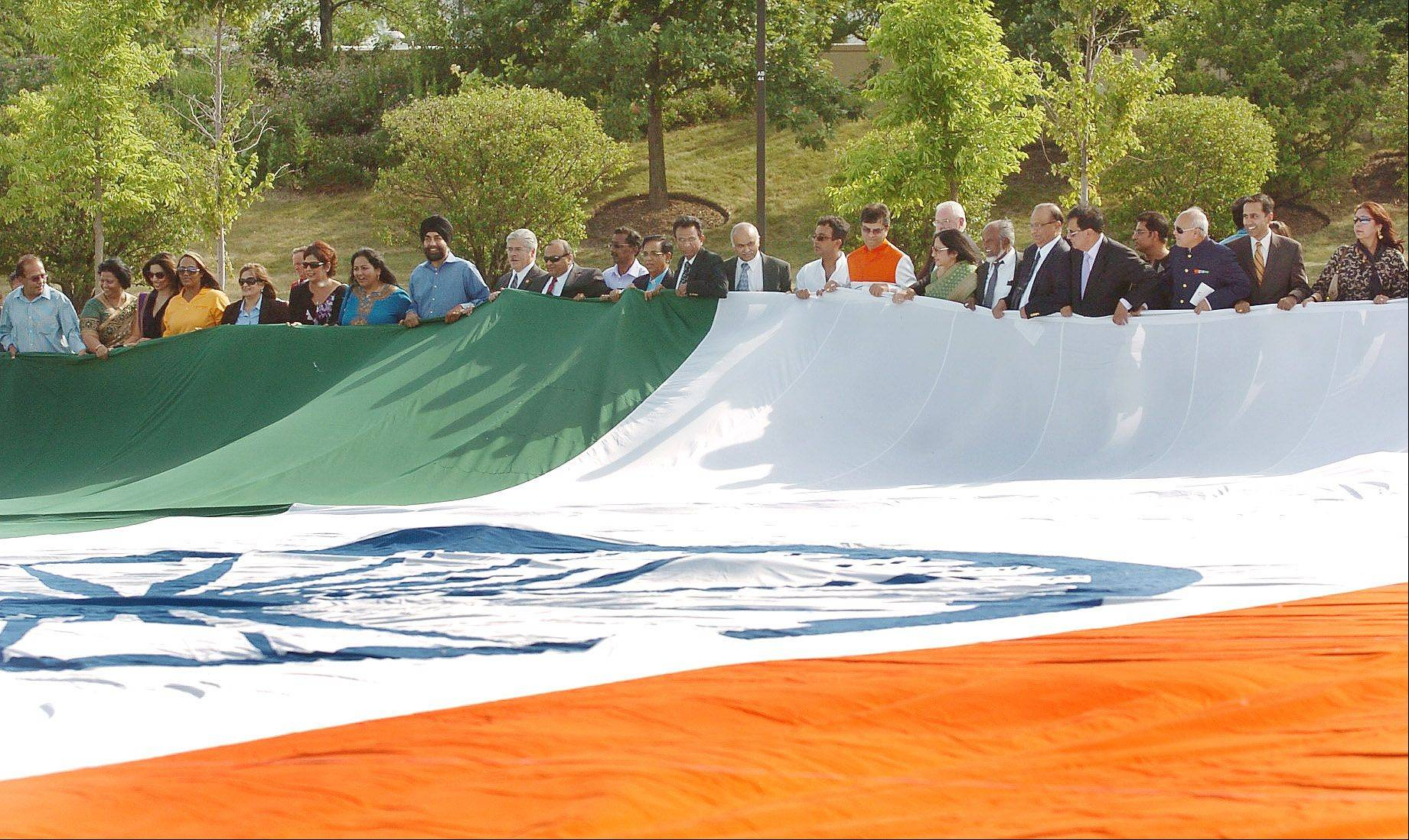 Community leaders unfurl the worlds-largest Indian flag in the parking lot of the Sears Centre, part of the Vibrant India fest in Hoffman Estates.