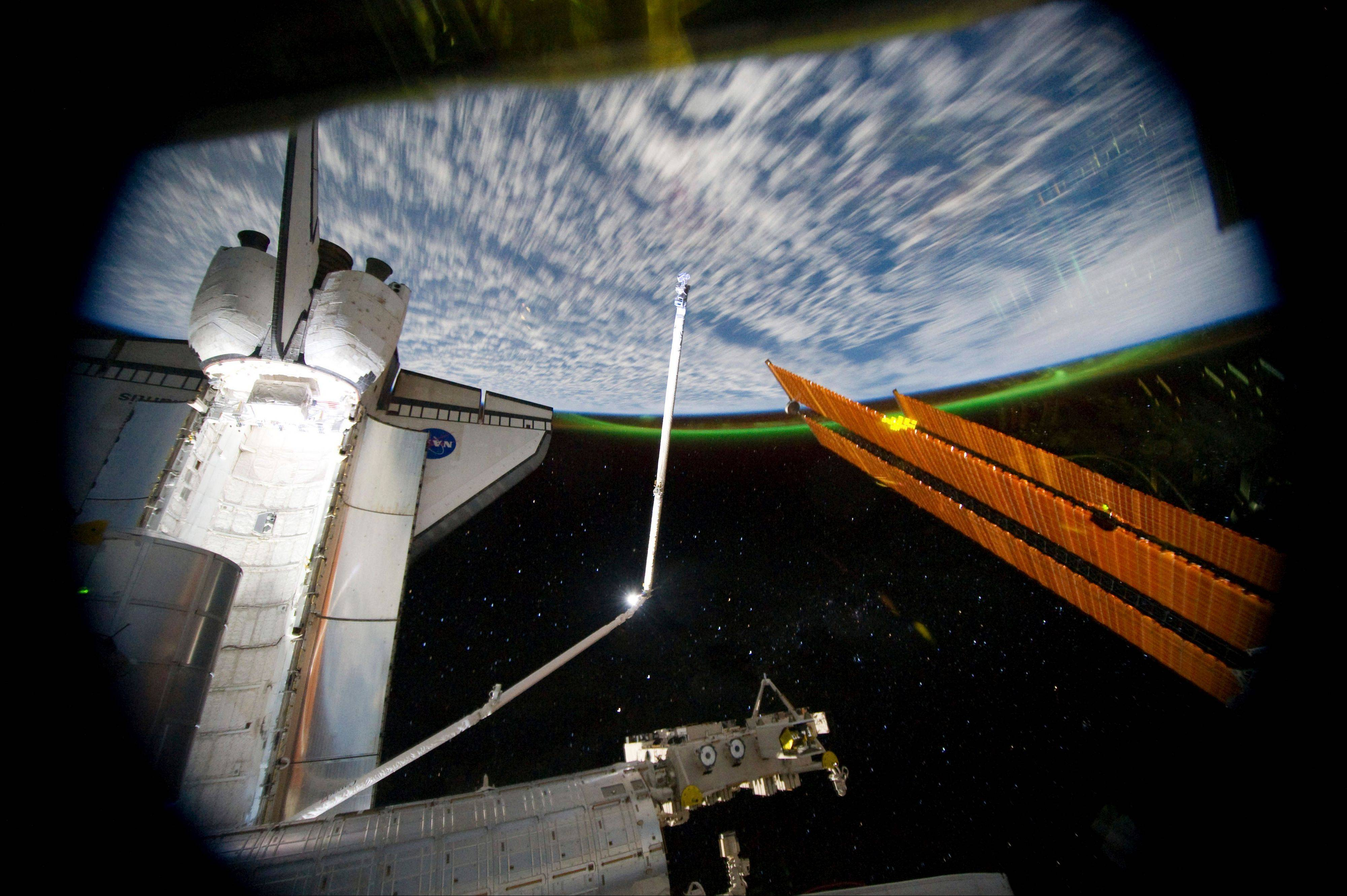 A view from the International Space Station, looking past the docked space shuttle Atlantis' cargo bay, and part of the station including a solar array panel. Aurora Australis, or the Southern Lights, can be seen on Earth's horizon.