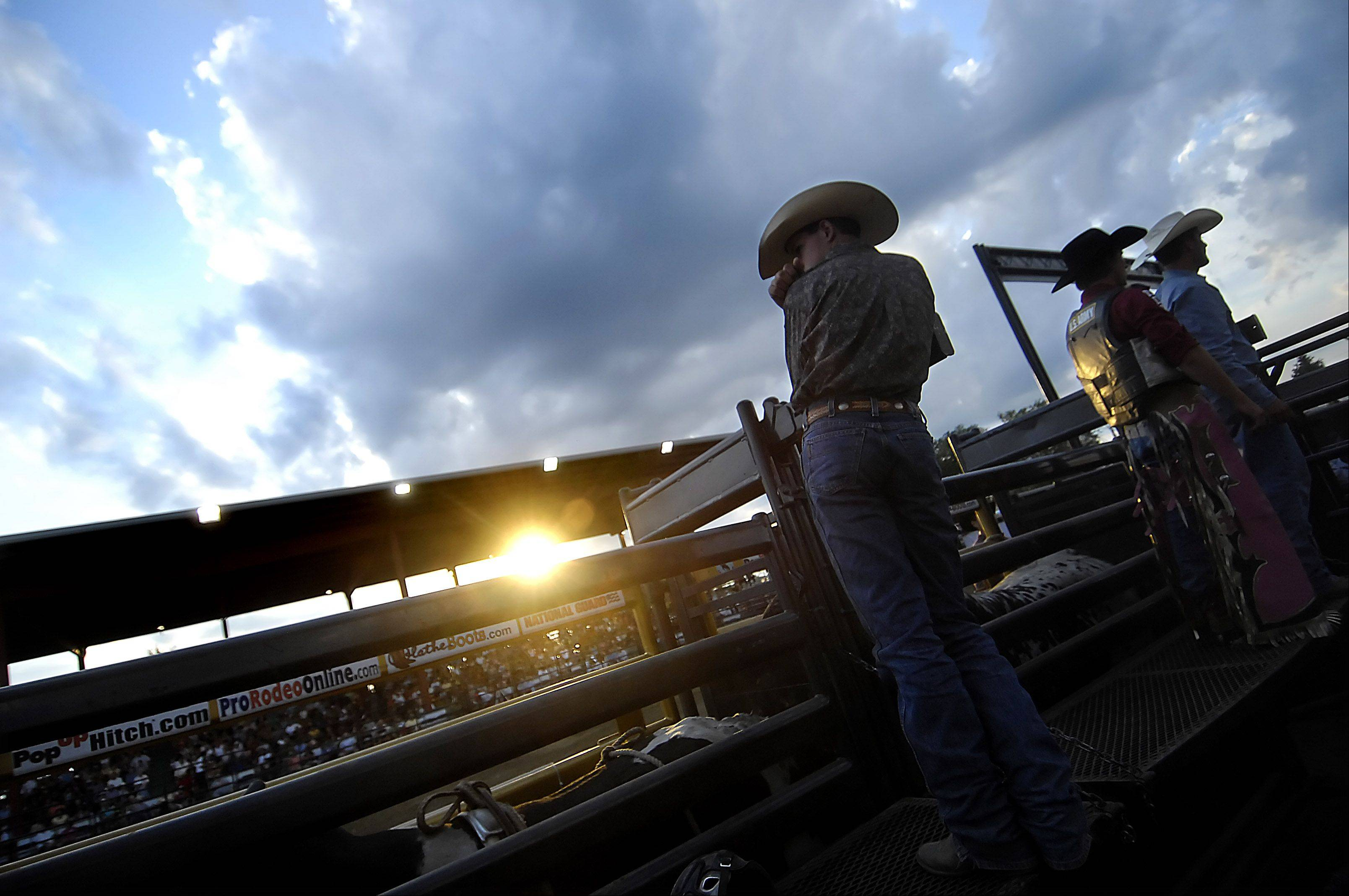 Cowboys stand on the chutes just before the start of the Championship Bull Riding event at the Kane County Fair.