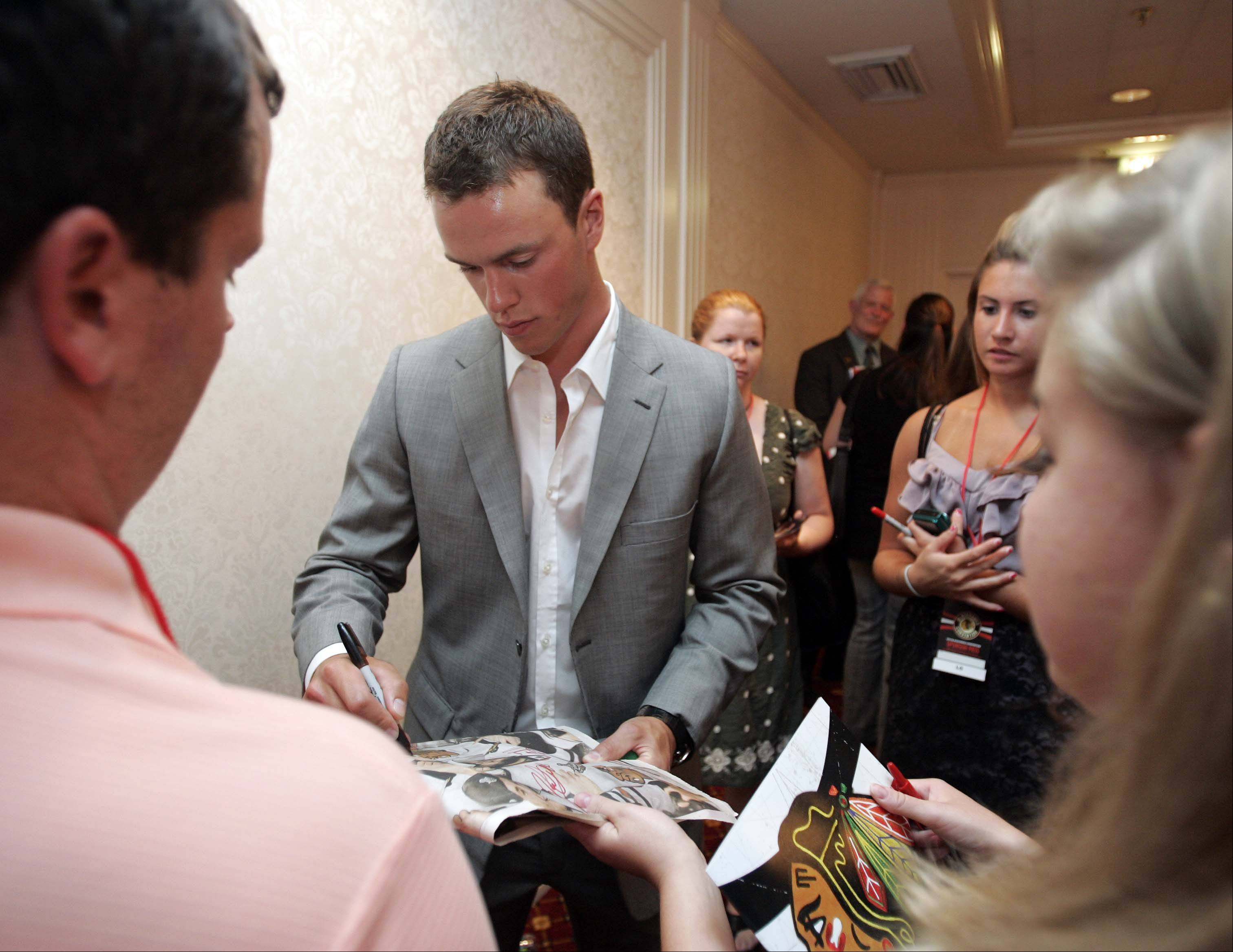 Jonathan Toews signs autographs for fans during the Blackhawks' fan convention.