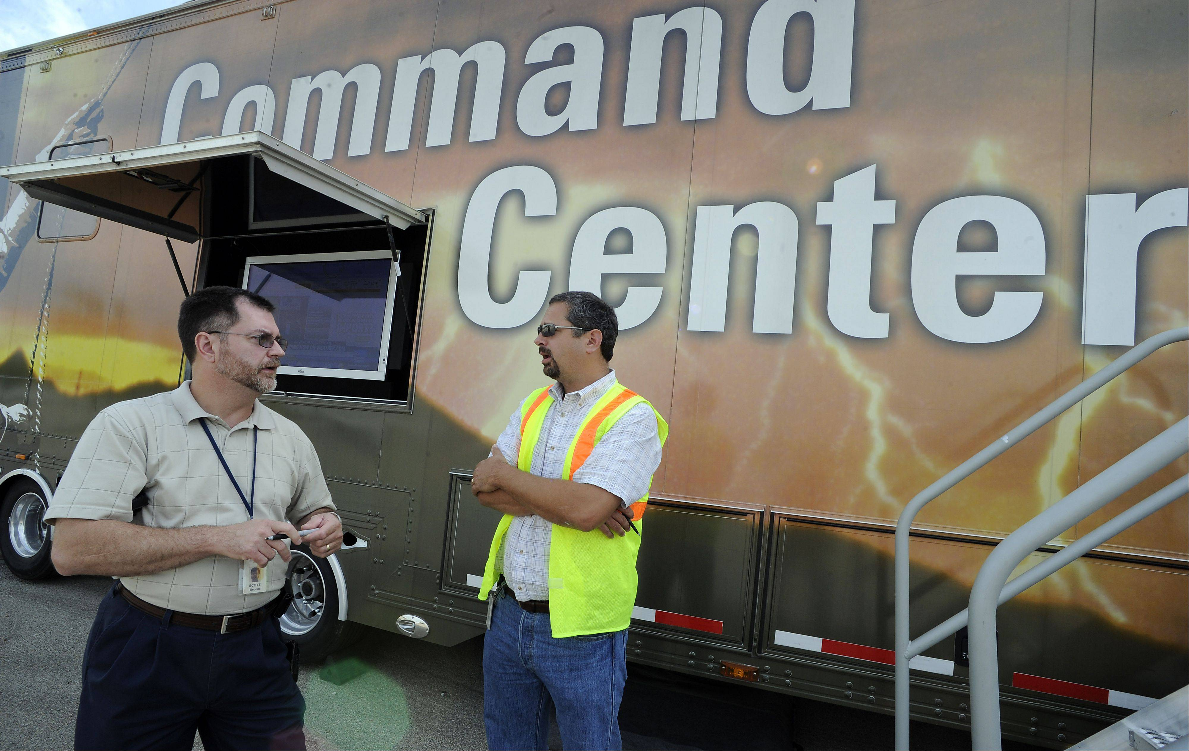 Mark Welsh/mwelsh@dailyherald.comDan Burer (right) Storm Team Leader and District Manger for Georgia Power talks with Scott Broom about areas that are still out in Lake County at Command Headquarters located at Gurnee Mills Mall on Saturday.