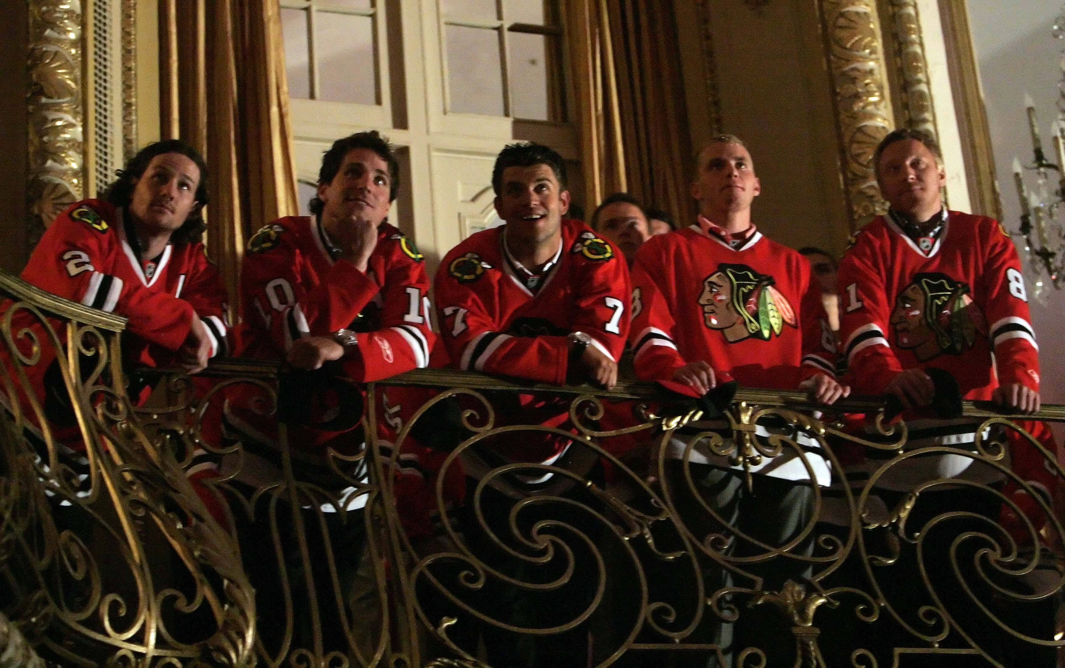 Duncan Keith, from left, Patrick Sharp, Brent Seabrook, Patrick Kane and Marian Hossa watch a video commemorating the team during opening ceremonies of the Blackhawks convention.