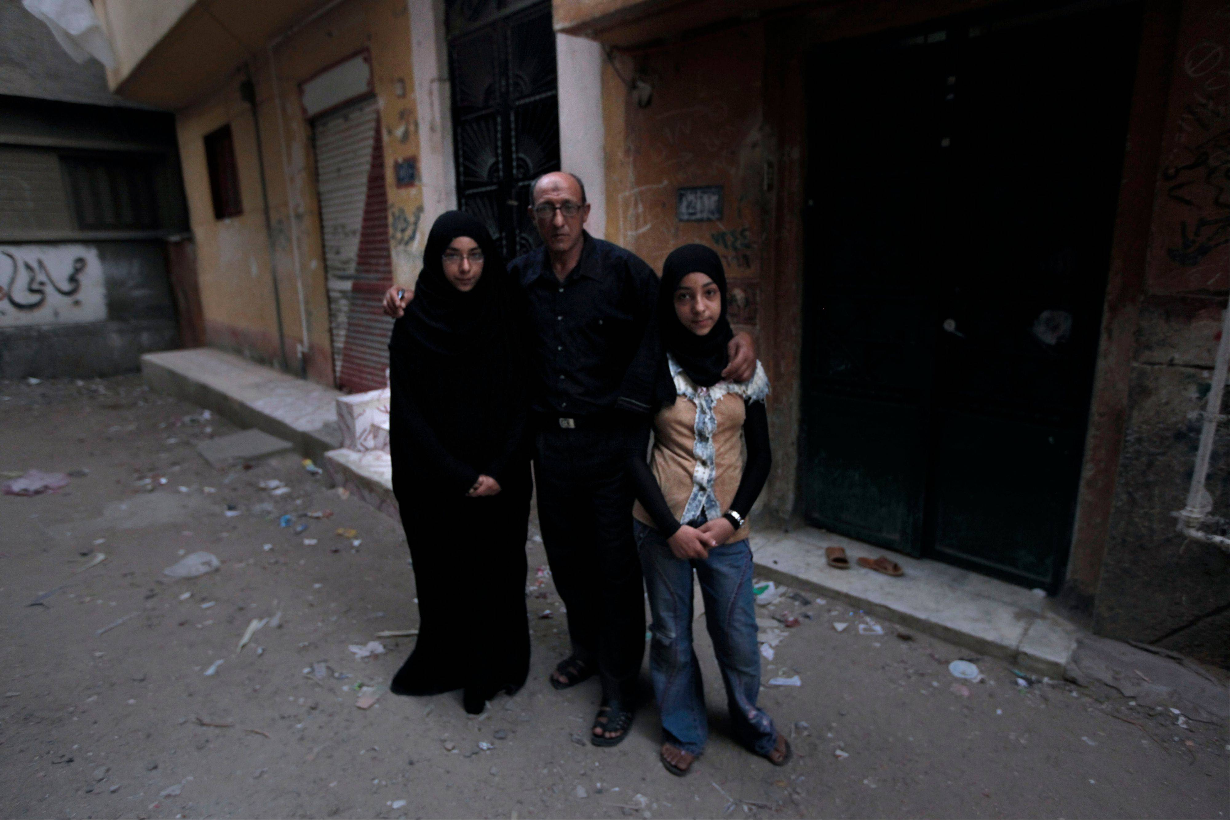 Family members of late Mariam Hawas, her daughters, Iman, 12, right, Fatmah, 16, left and her husband Bayoumi Abdel-Latif Bayoumi, center pose for a photo in front of the family house in Talkha, Mansoura, Egypt. Hawans lost her life trying to collect her monthly salary. Egyptians have long complained that the cheapest thing in this country is their lives. Under the former regime, wages in the public sector, the single largest employer, were miserably low and the already vast gap between rich and poor only widened.