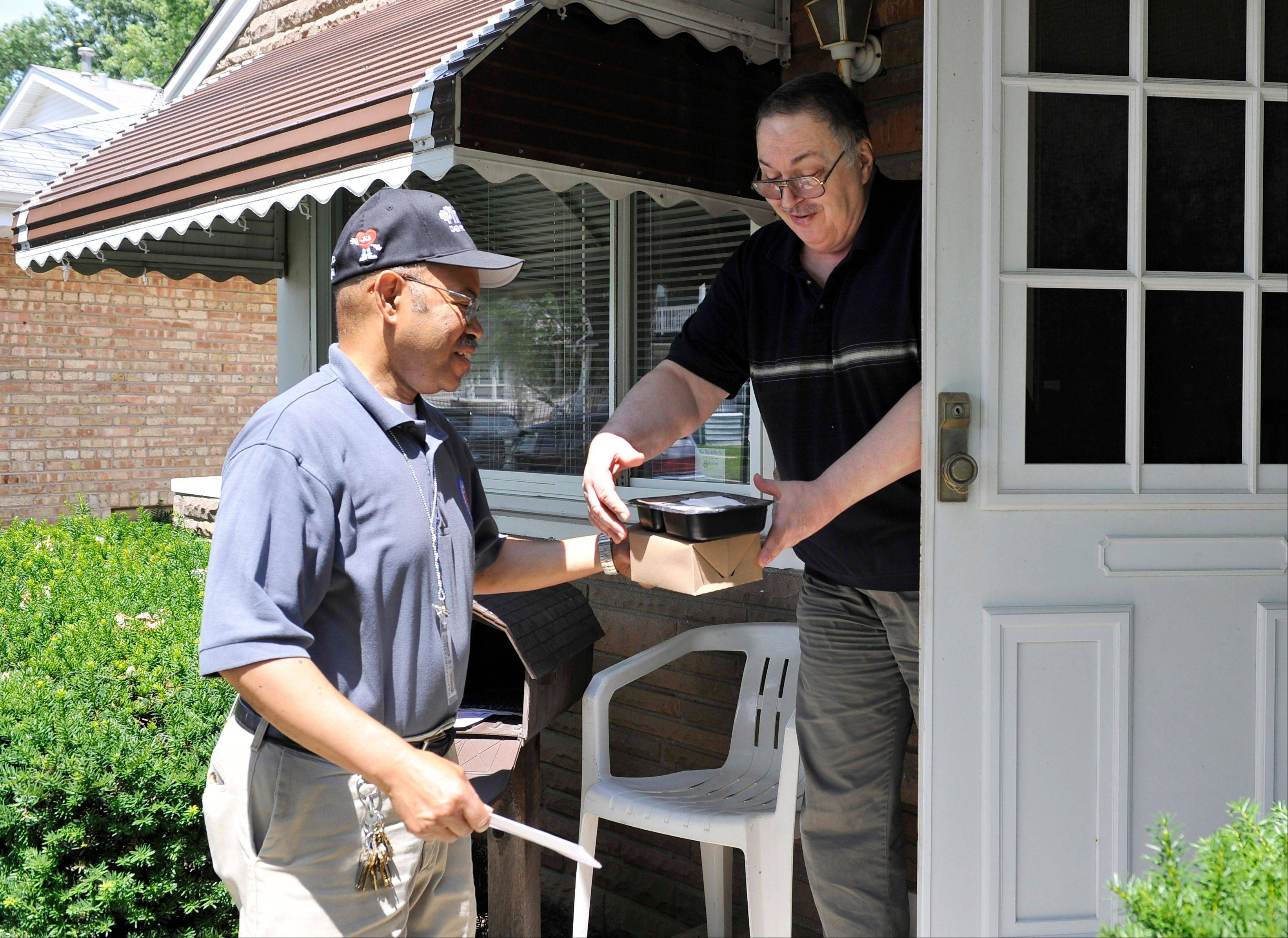 Township of Proviso employee Chester Lamar delivers a meal to Joe Lagen, 67, who suffers from vertigo and cannot drive in Bellwood. Budget cuts to programs that deliver meals to homebound seniors in Illinois may force some frail elderly into nursing homes, a more expensive option for both the individuals and the state, advocates say.
