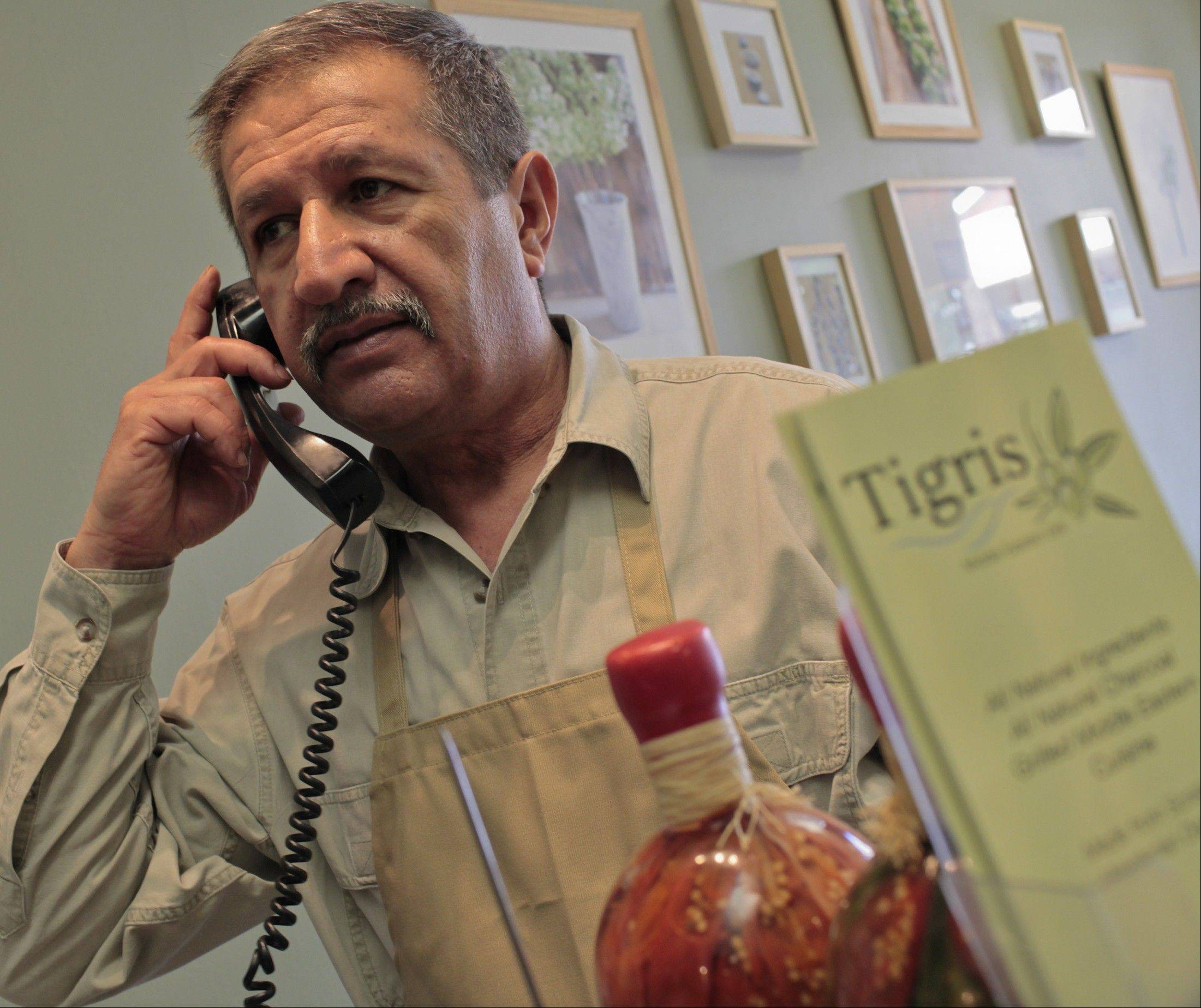 "Mowafak Alshagra, who coached Iraq's water polo team, at work at Tigris, the Oakton, Va., restaurant he opened three years ago. ""Just in my deep inside, I feel a little bit sad when (Iraqi customers) see me inside the kitchen and not coaching."""