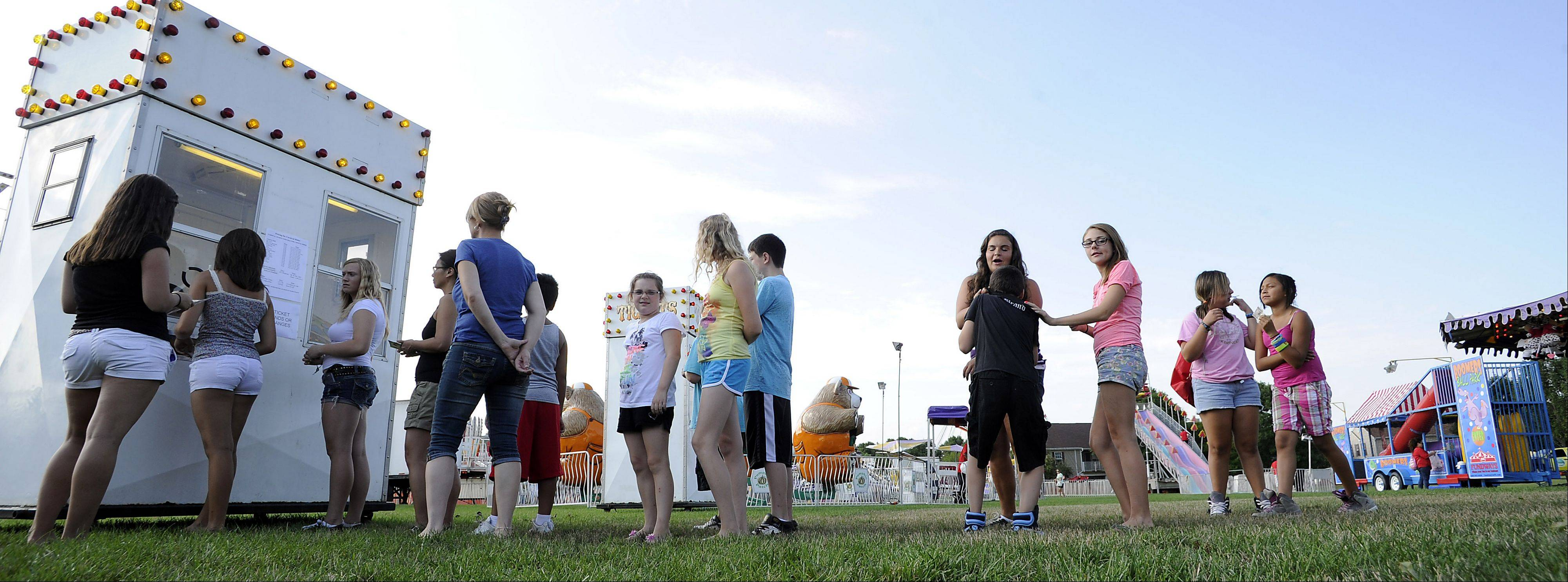 Kids wait in lines to buy ride tickets at the Streamwood Summer Celebration on Friday.