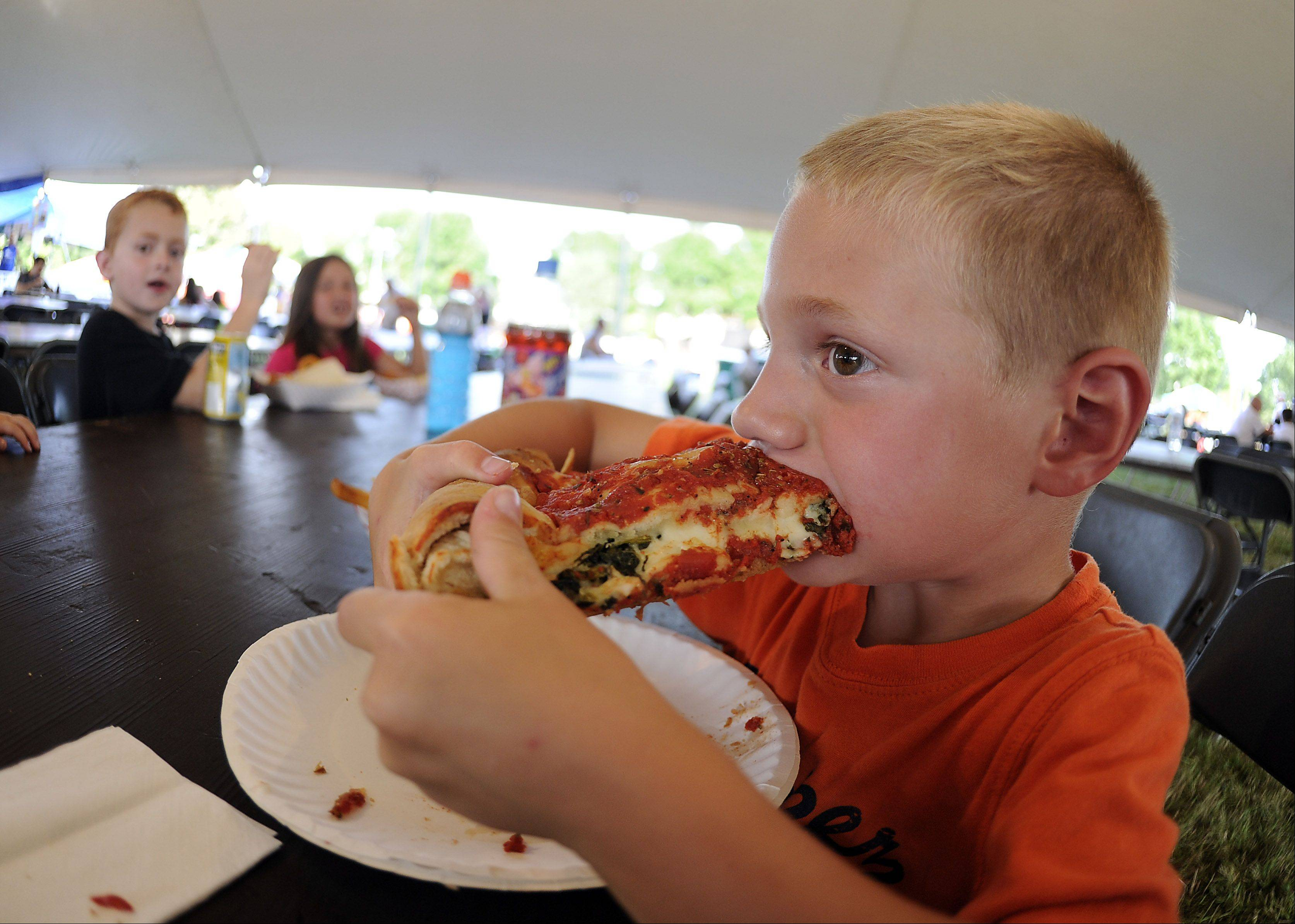 Zachary Flosi of St. Charles chows down on some Chicago-style pizza at the Streamwood Summer Celebration on Friday.