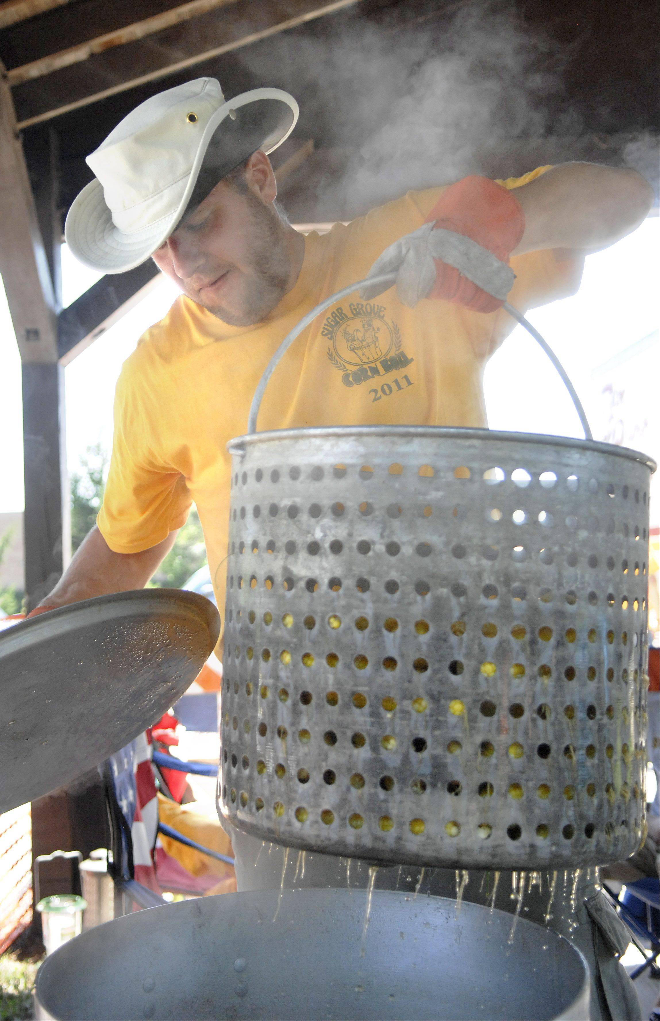 Andrew Drabik of Aurora pulls out a cooked batch of sweet corn at the Sugar Grove Corn Boil in Volunteer Park on Saturday, July 30. This is Drabik's second year volunteering for the Boil. Each pot holds about 50 ears and takes 10 minutes to cook. 11,000 ears of corn will be made over the three day festival.