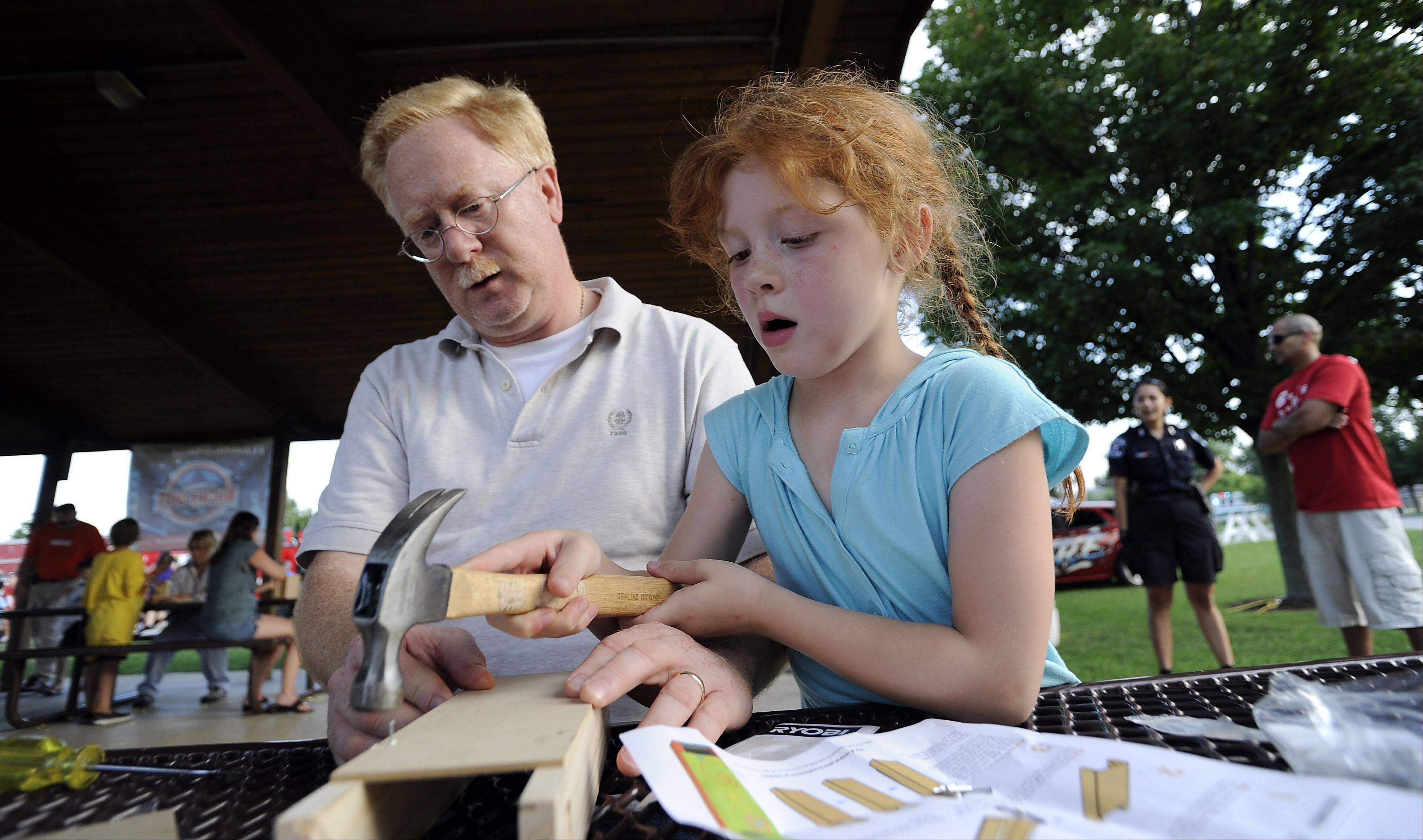 Don Llewellyn and his daughter Caitlyn, 6, construct a wooden periscope as part of Bartlett's celebration of National Night Out on Friday.
