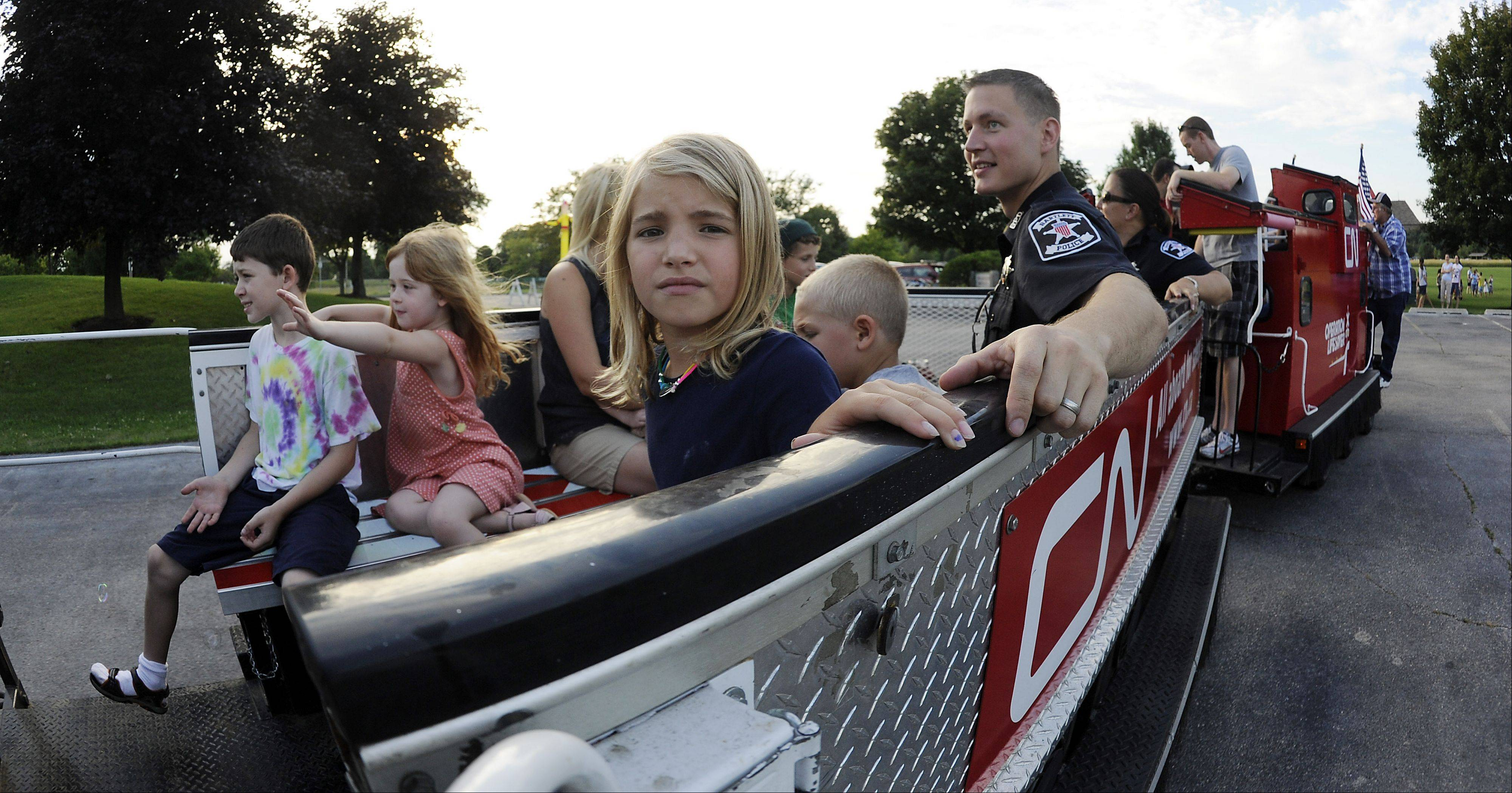 Olivia Kyes, 8, of Kansas rides the miniature Canadian National locomotive called Little Obie as part of Bartlett's celebration of National Night Out. Kyes is in town visiting her grandparents.
