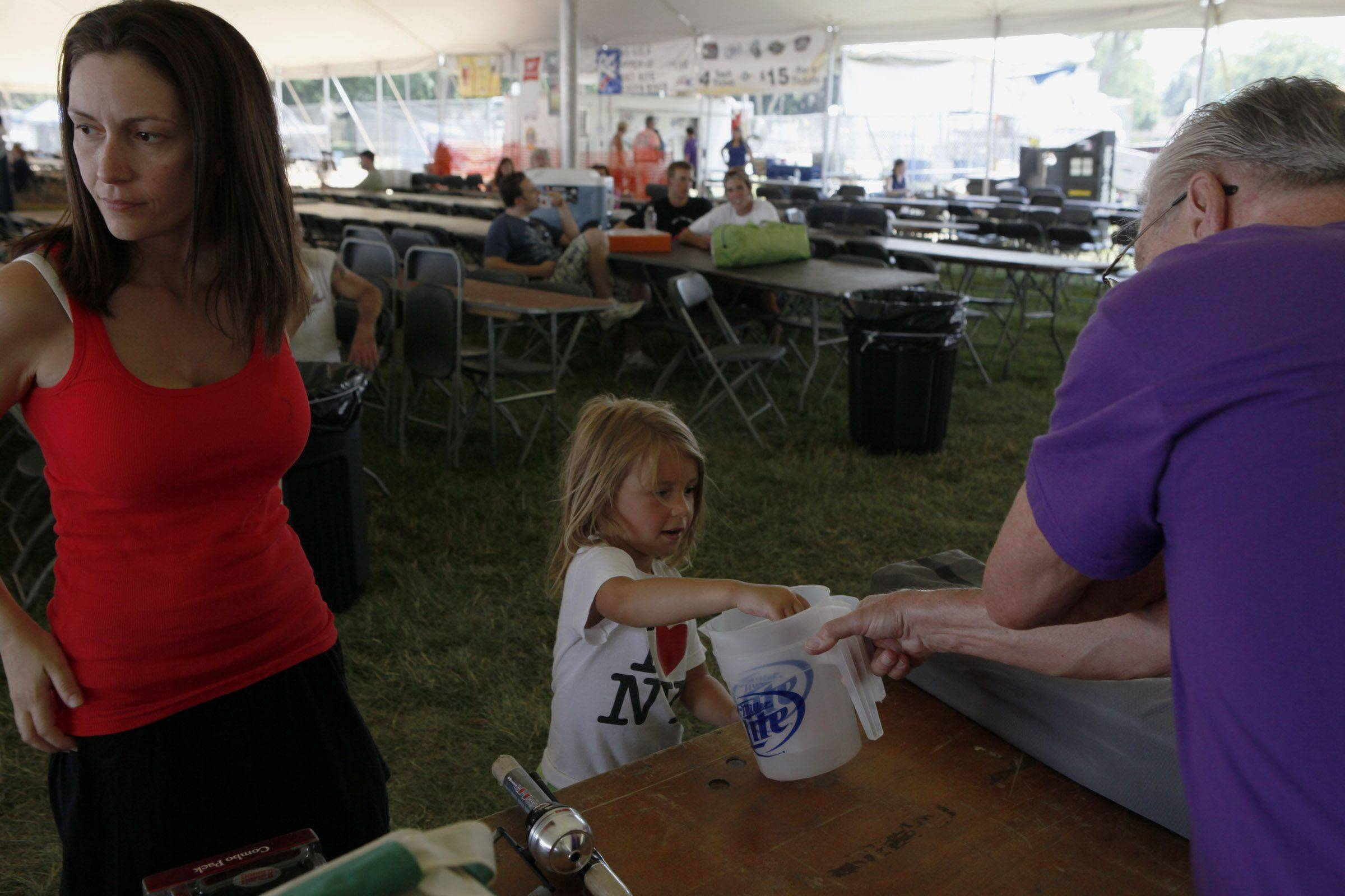Emma Caniglia won the last drawing, so she got to pull the next ticket in Sunday's Happy Acre Fishing Derby prize giveaway Sunday during Itasca Fest. Her mom, Marianne, left, helped her pick out a prize.