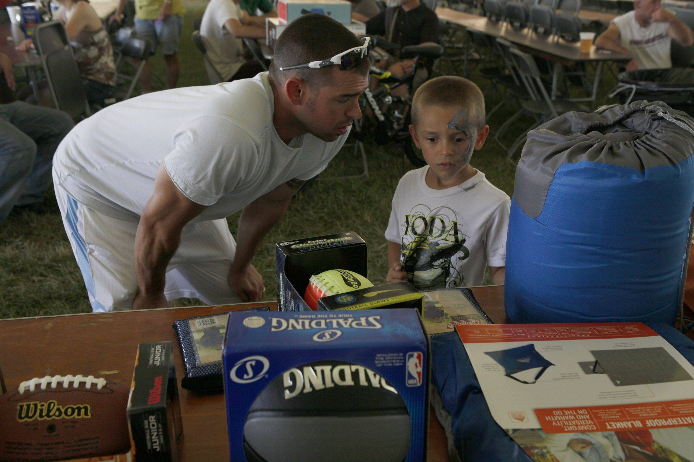 Brandon Caniglia and his father, Terry, pick out a prize in the Happy Acre Fishing Derby prize giveaway Sunday at Itasca Fest.
