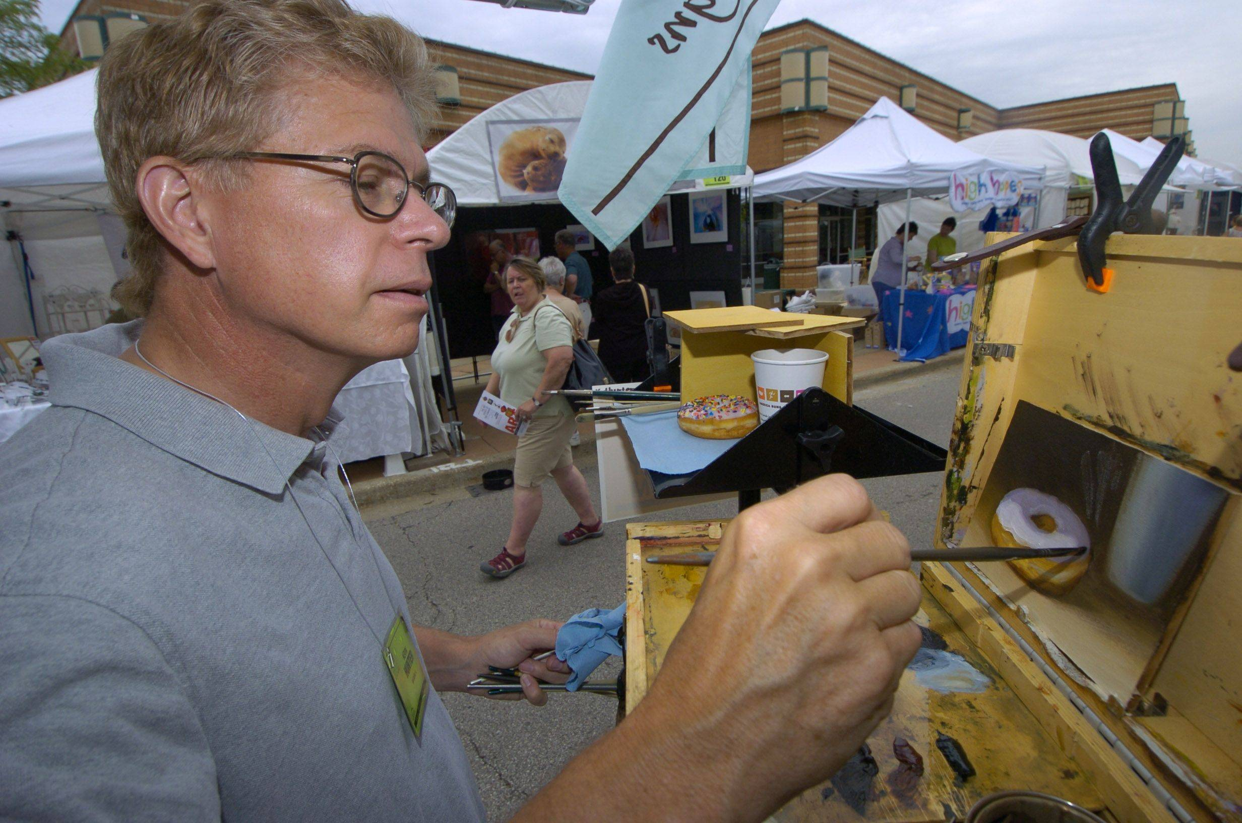 Artist Kevin Hunter of Batavia paints while using a sprinkled doughnut as a model during the Buffalo Grove Invitational Arts Festival Saturday.