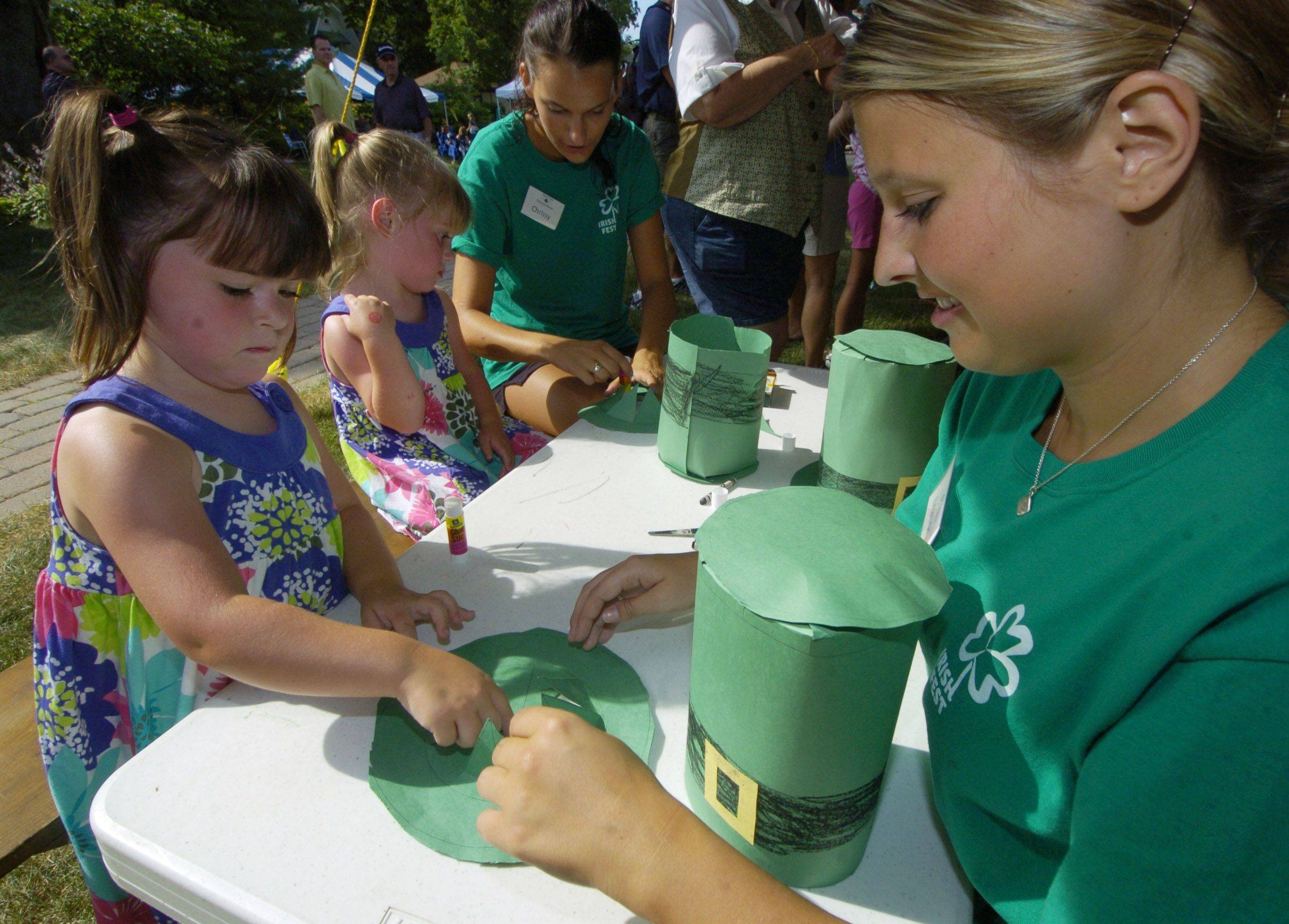 Shannon Kenney, age 4-1/2, of Barrington, front, works on an paper Irish hat with park district intern Mallory Volocyk, while her twin sister Samantha works with intern Chrissy Tiske during Arlington Heights Irish Fest Saturday.