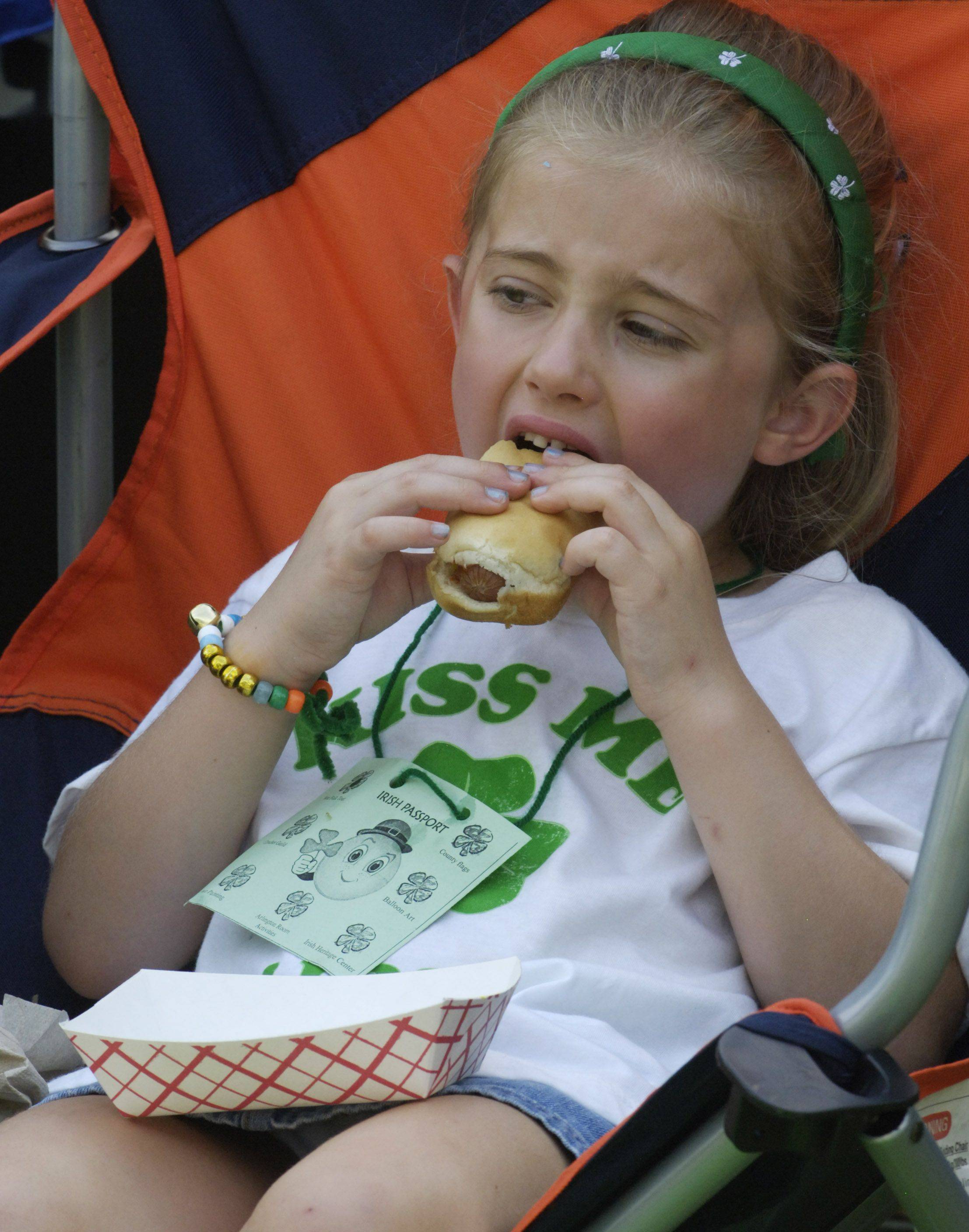 Margaret Miller, 5, of Arlington Heights enjoys a hot dog while watching a band during Arlington Heights Irish Fest Saturday.