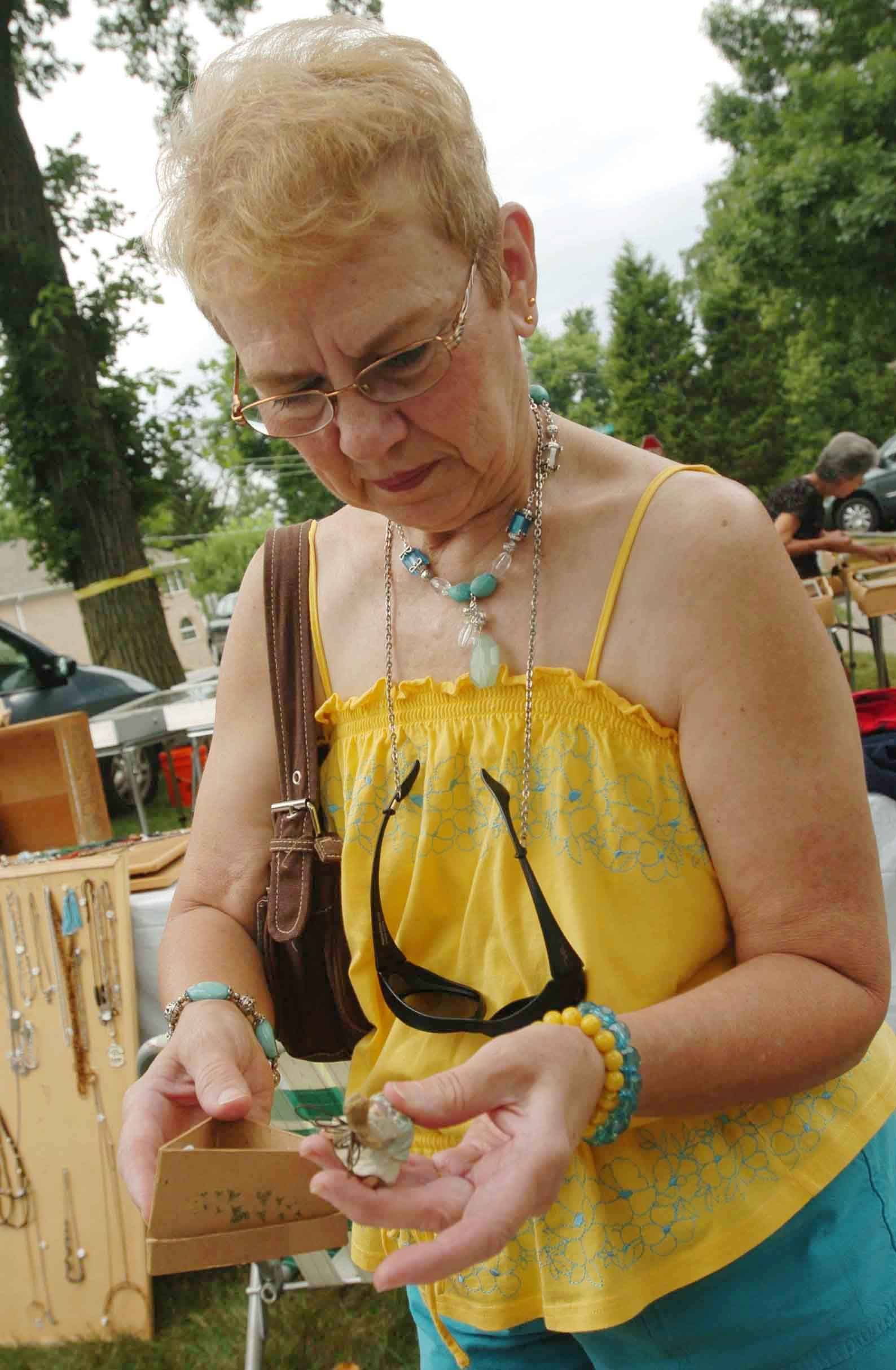 Cheryle Rizzo of Burbank looks at an angle ornament during the antique flea market at Washington Park during Itasca fest Saturday.
