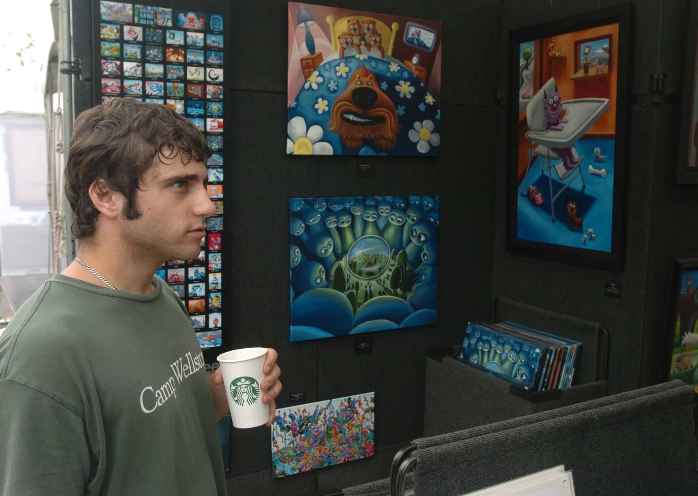 Evan Graves of Chicago looks at paintings by Melvin McGee at Yorktown Center in Lombard Saturday.