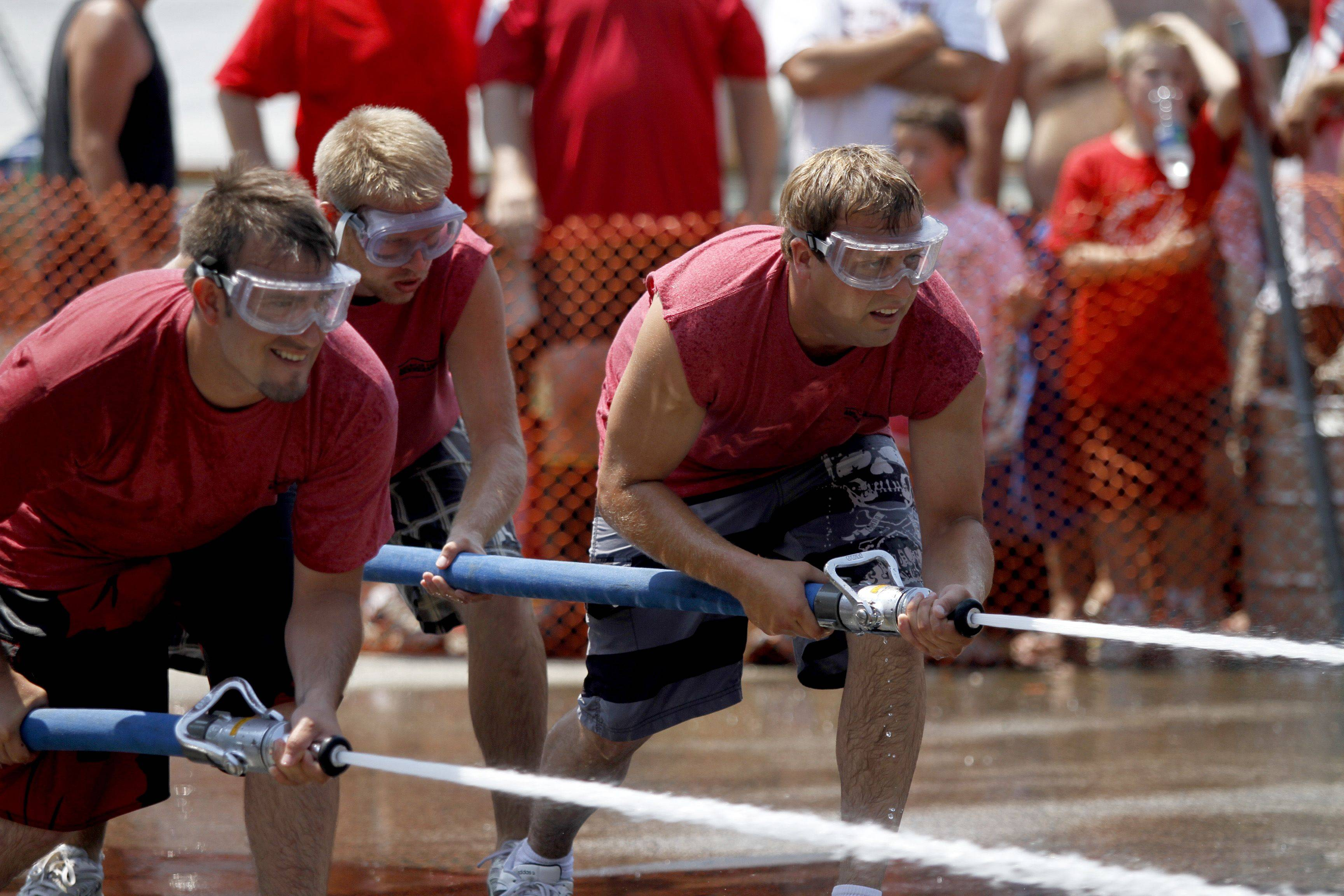 Nick Ray, right, Zach Willamas, middle, and Danny Carole, left, all from Fox Lake, compete in a water fight Sunday afternoon for the Fireman's festival. Teams had a two minute heat to get a barrel onto the other teams side.