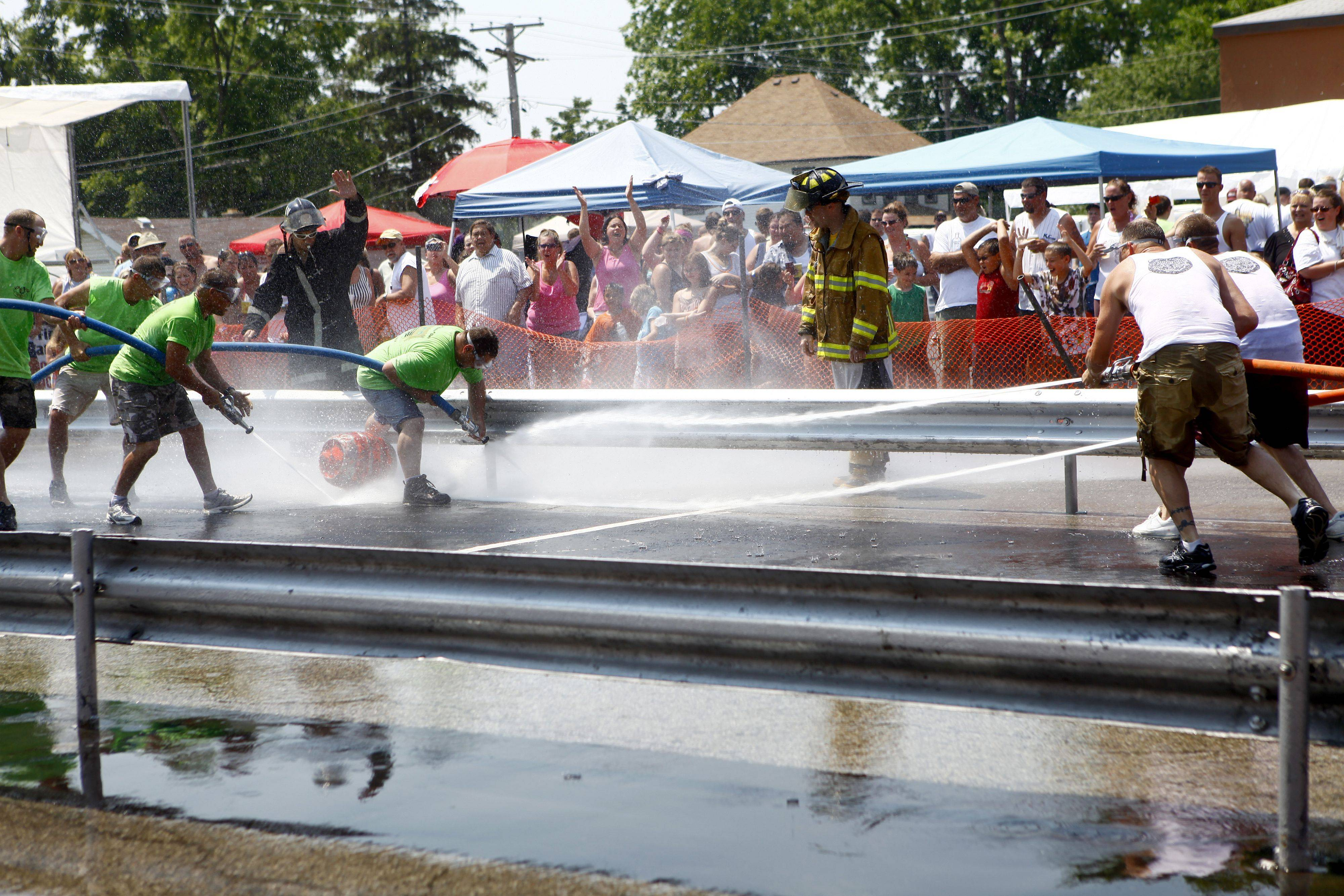 Lake Villa fire fighters referee the water fights at the annual Fireman's festival Sunday afternoon in Fox Lake. The fest went on all day and included food, games and water fights for entertainment.
