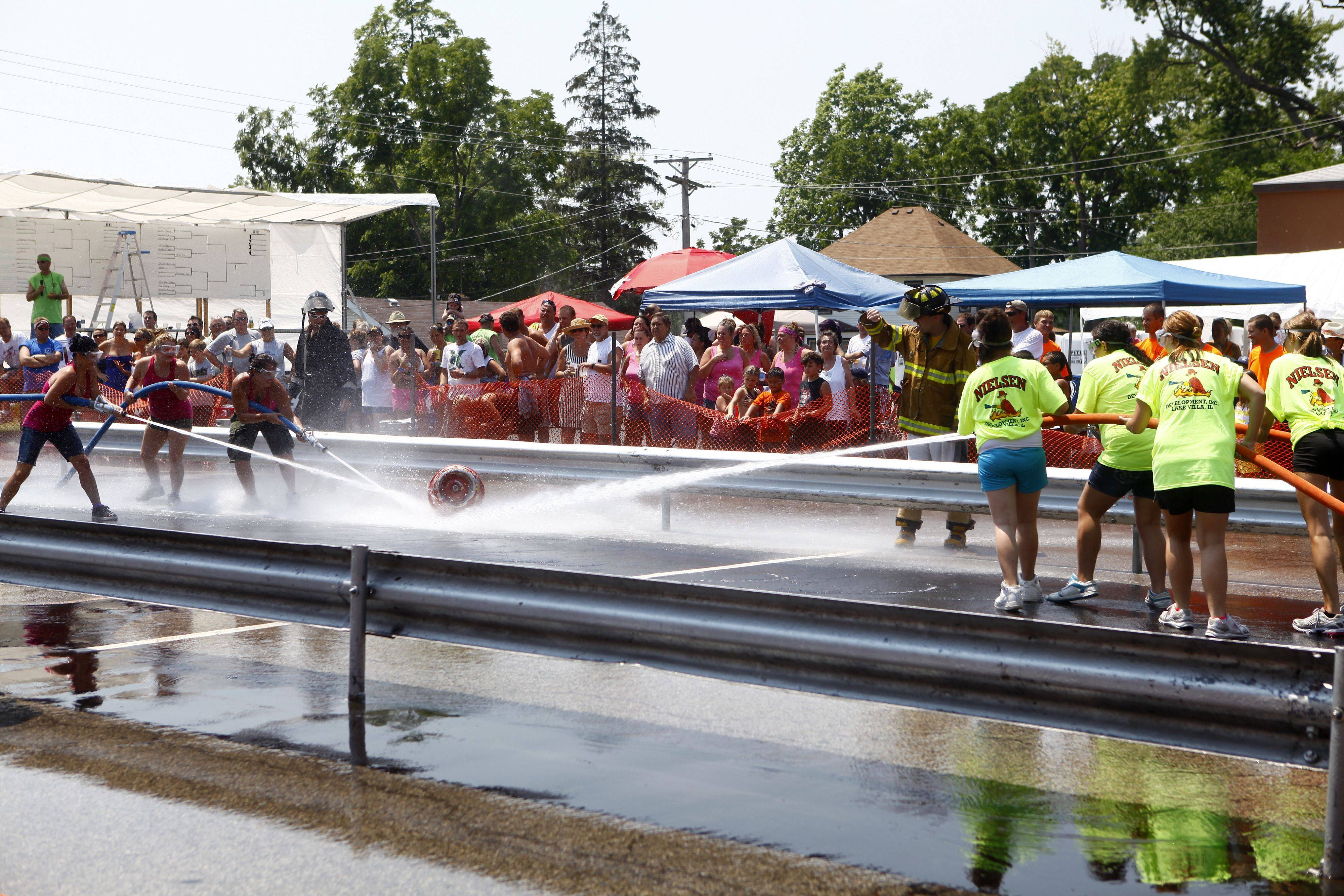 Two teams compete in a water fight during the annual Fireman's festival Sunday afternoon in Fox Lake. The festival went on all day with food and water fights.