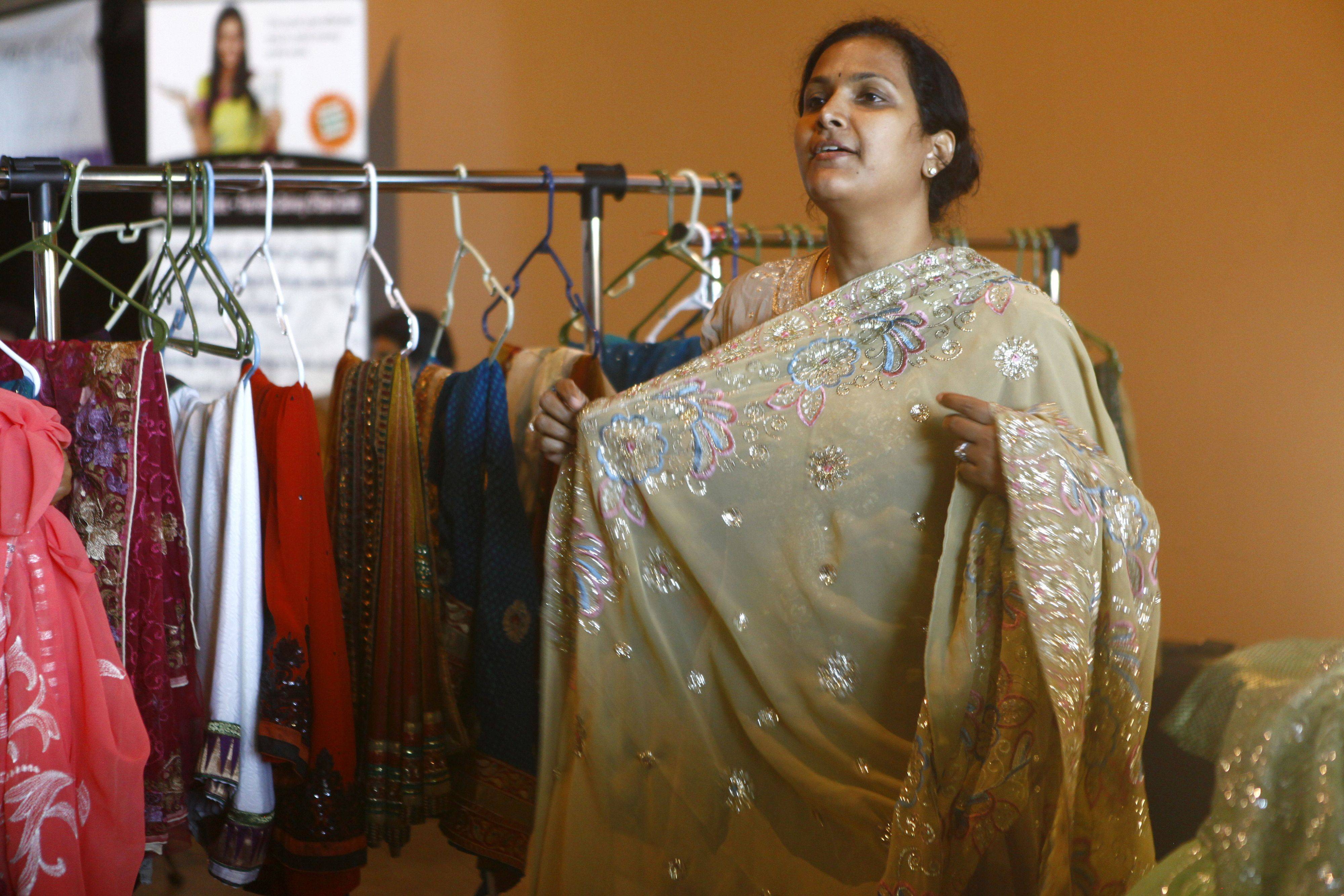 Reddy Anu, from Delhi, India, shows customers one of her handmade saris at the Vibrant India Festival held at the Sears Center Sunday afternoon. The fest featured music, food, clothing and jewelry vendors.
