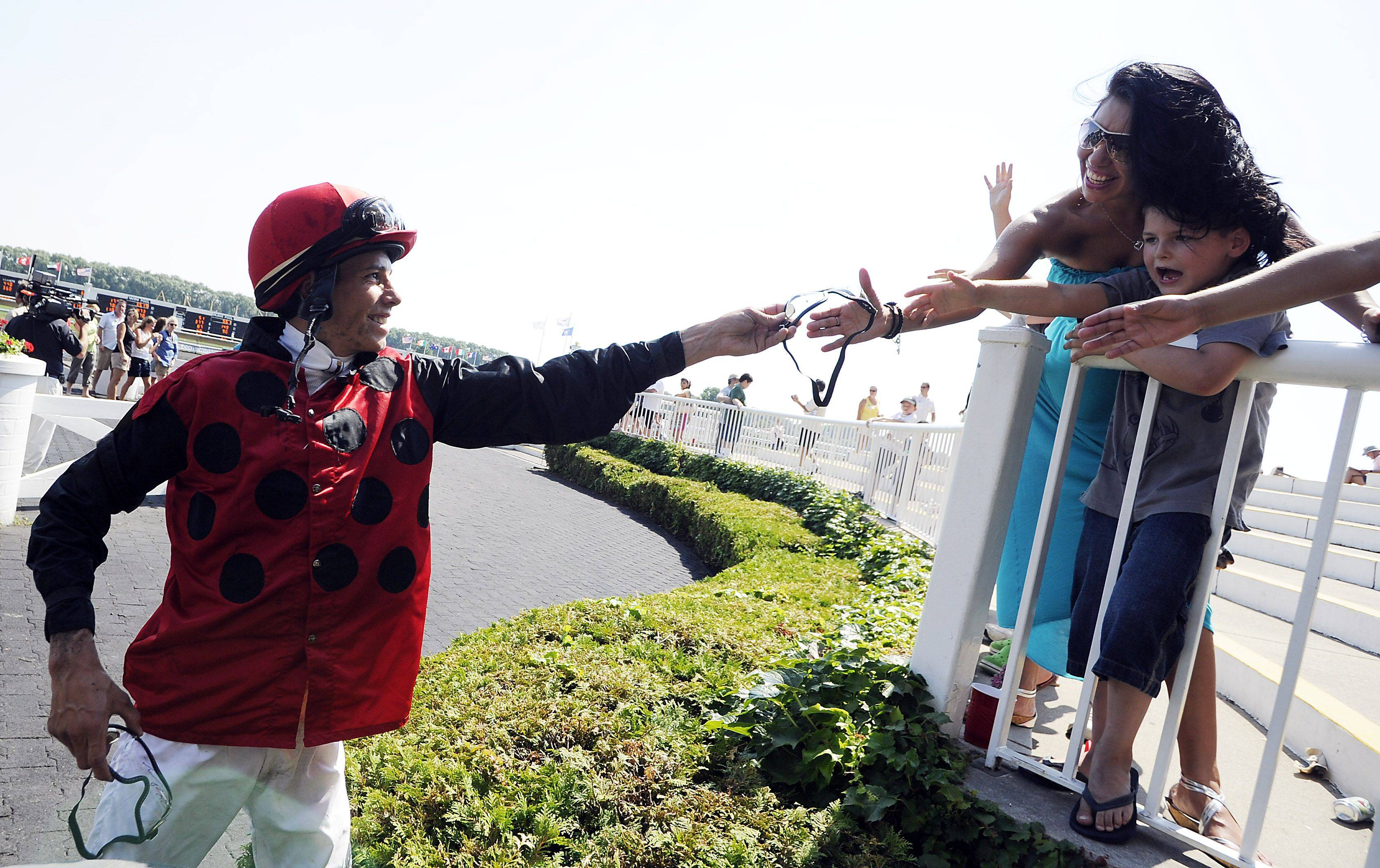 Jockey Tanner Riggs hands his goggles to Steven Horvtha V and his mom Marcie Sanchez of Berwyn after he won the fifth race at the Fiesta in the Park party at Arlington Race course on Sunday.