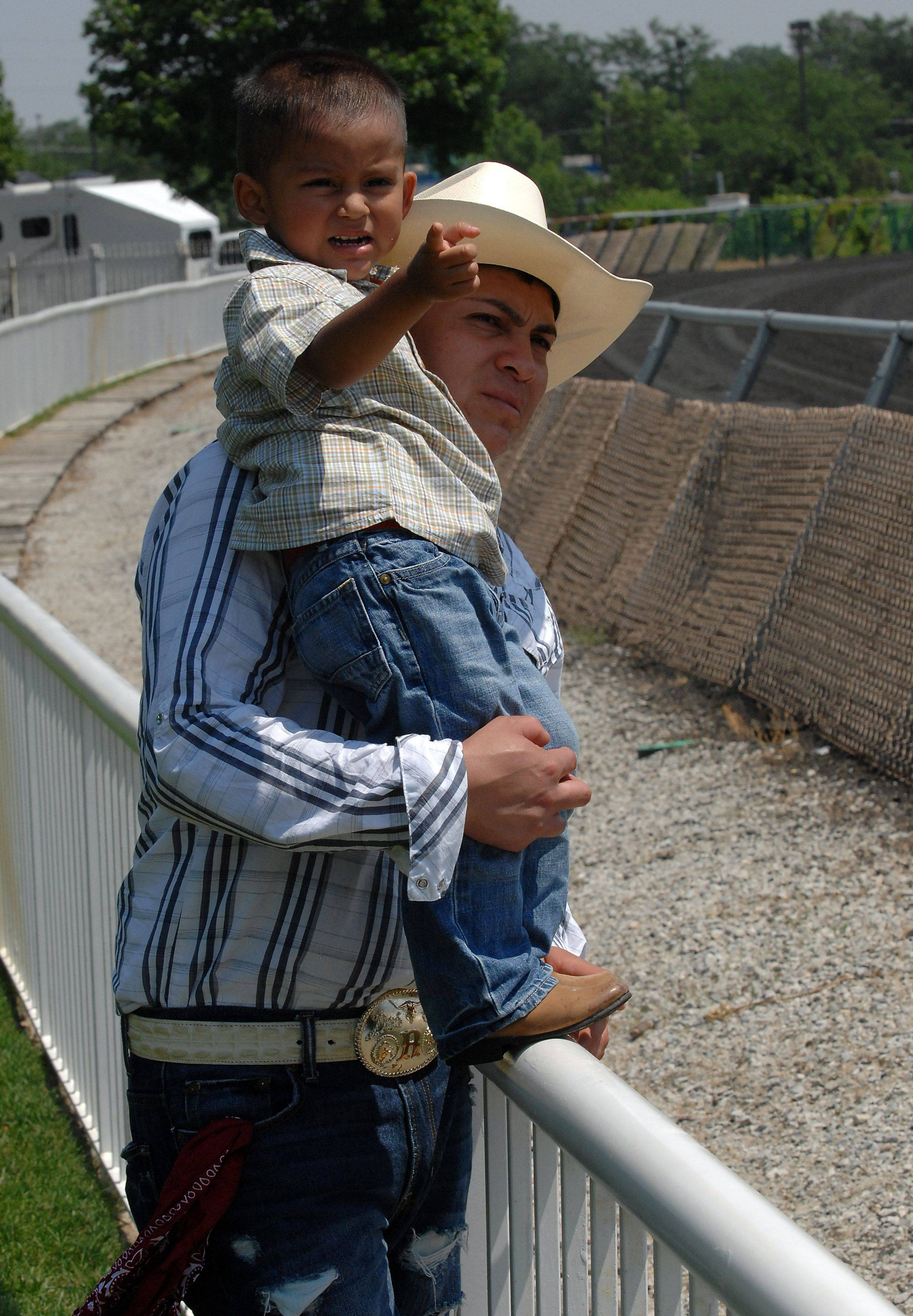 Enjoying the second race is Jose and his son Diago, 2, of Addison as they watch the ponies fly down the track at the Fiesta in the Park party at Arlington Race course on Sunday.