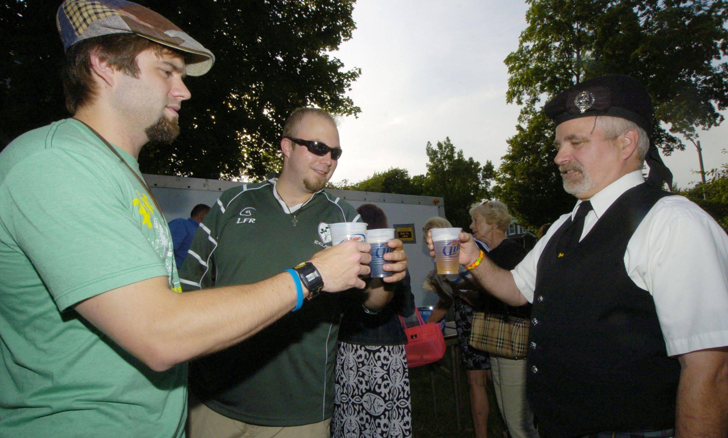 Left to right, Badalamenti and Peter O'Neal, both of Palatine share a toast with Marty Maneck of the Glengale Pipes and Drums of Des Plaines, while having a beer together during Irish Fest in Arlington Heights Friday.