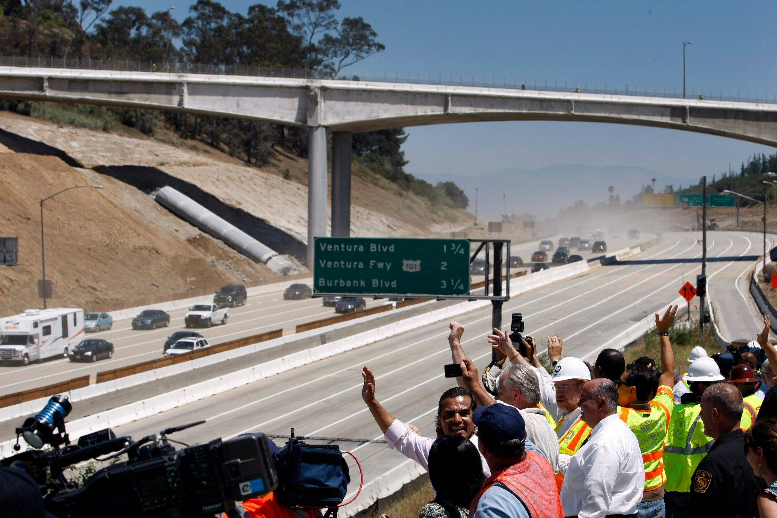 Los Angeles Mayor Antonio Villaraigosa, left, and other officials celebrate the demolition of two lanes of the Mulholland Drive bridge over Interstate 405 ahead of schedule in Los Angeles on Sunday.