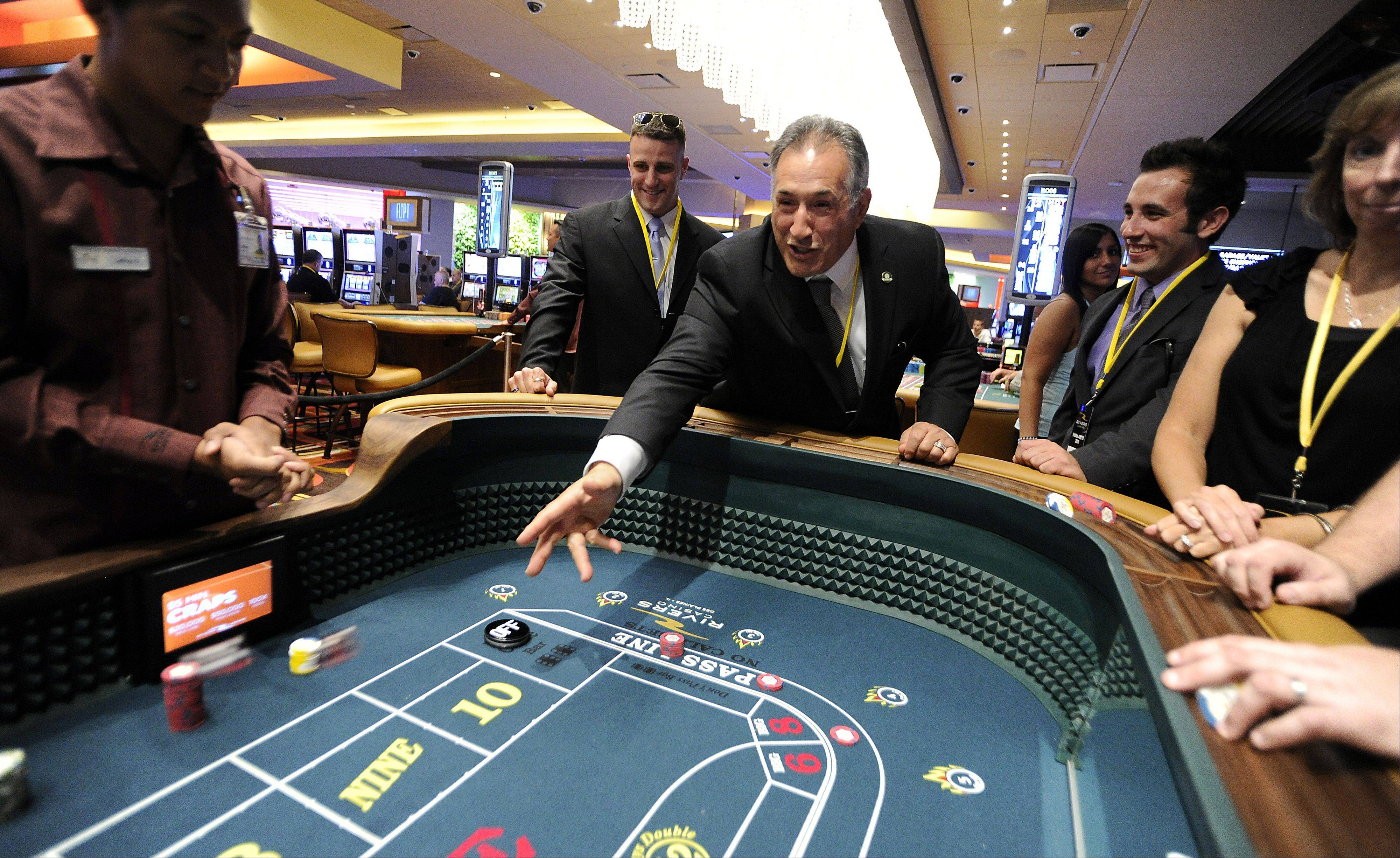 Des Plaines Mayor Martin Moylan throws the dice at 5 pm to signal the opening of the Rivers Casino.