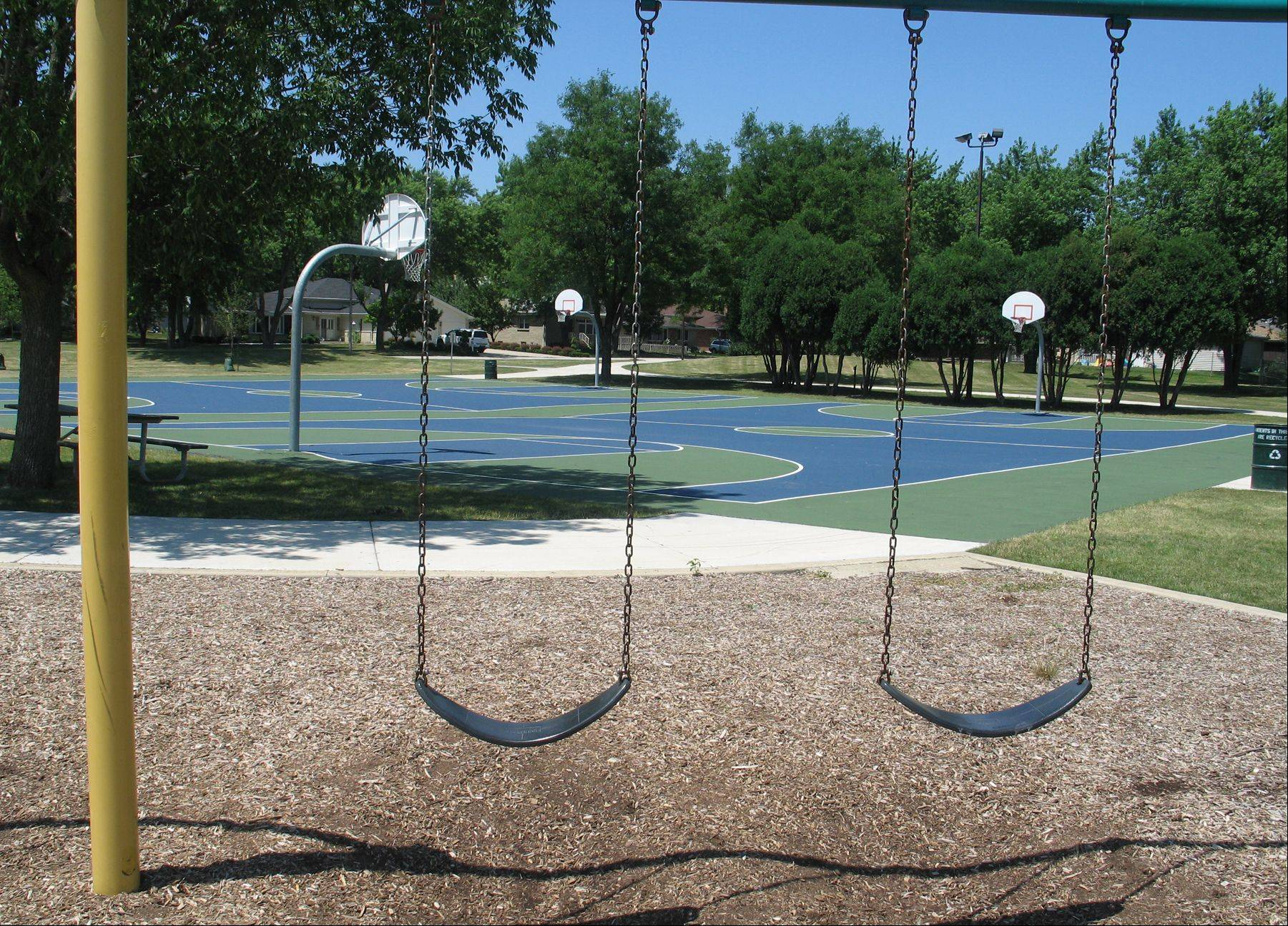 Even on the many perfect summer days this month, kids playing by themselves are an endangered species in the suburbs. These empty swings and basketball courts of Carefree Park in Arlington Heights are typical.