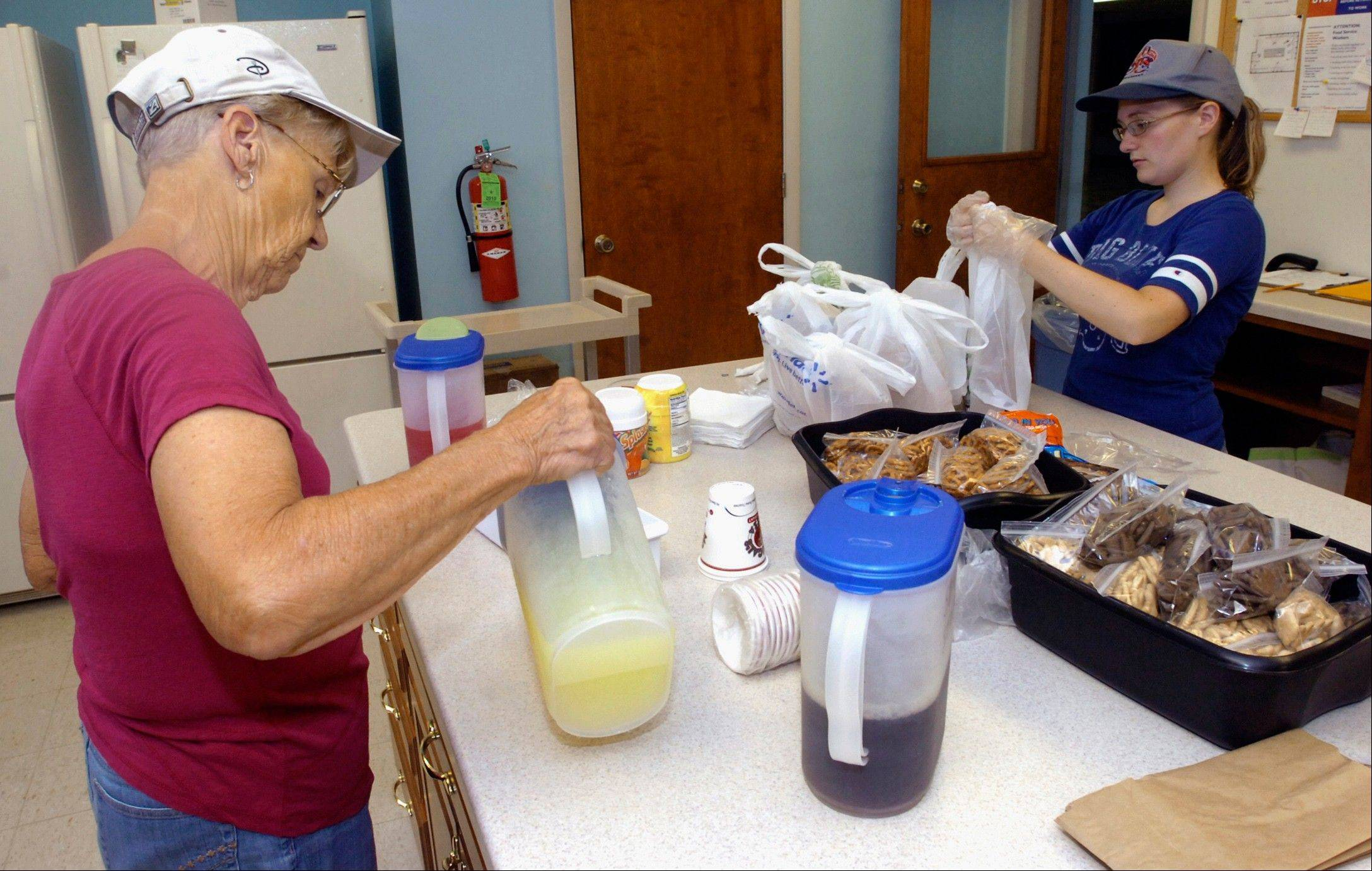 Volunteers Gail Bower and Katie Stoltz fill drinks and put the finishing touches on lunches-to-go at the Soup Stop in the basement of the First Presbyterian Church in Charleston, Ill. The idea for this soup kitchen-style non-profit group was conceived by Rev. Susan Reichenberg as a way to serve those who might otherwise go hungry.