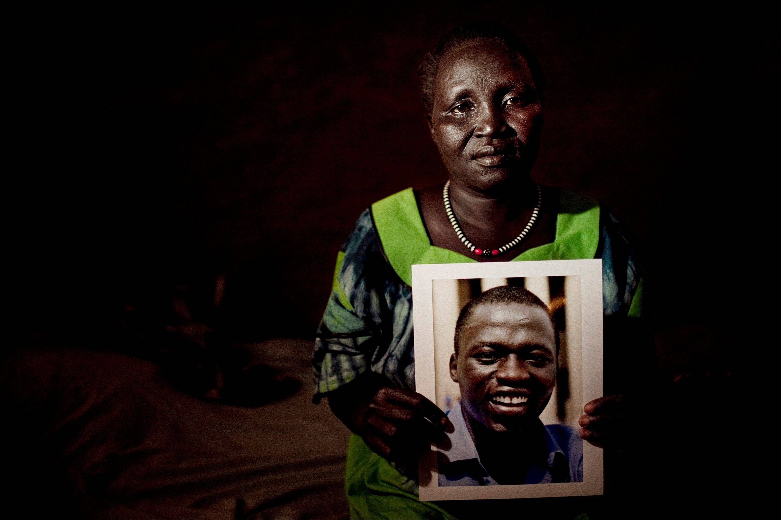 Morris Michael's mother, Elizabeth, poses with a recently-made portrait of her son inside her home in the Kakuma refugee camp in northern Kenya. She has not seen Morris, or a recent image of him, since he moved from Kenya to the United States in 2003. The family has lived as refugees in Kakuma since they fled war in neighboring Southern Sudan in 1993.