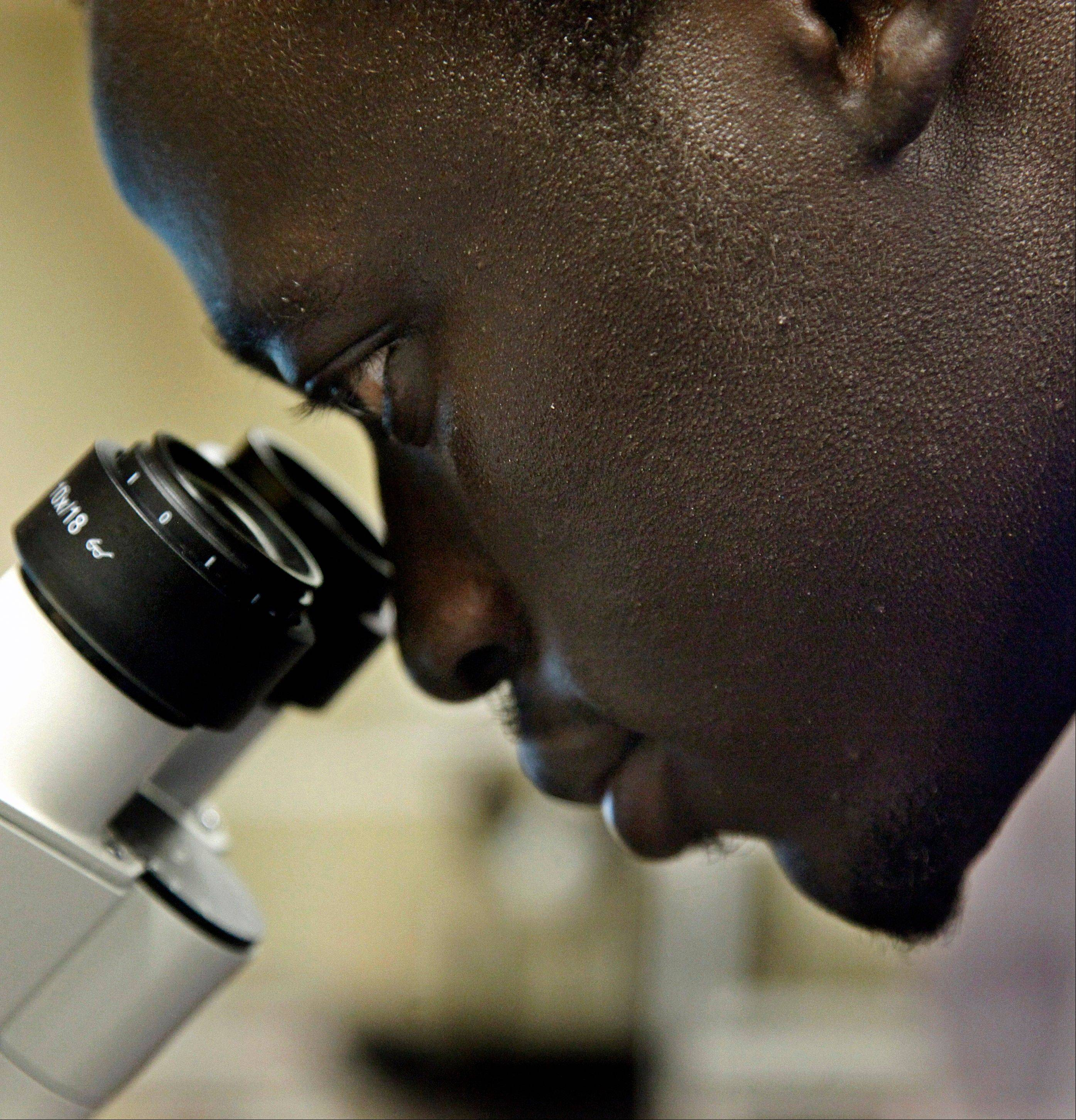 Morris Kaunda Michael, 22, a biomedical engineer, peers into a microscope at Columbia University's biomedical engineering lab in New York.
