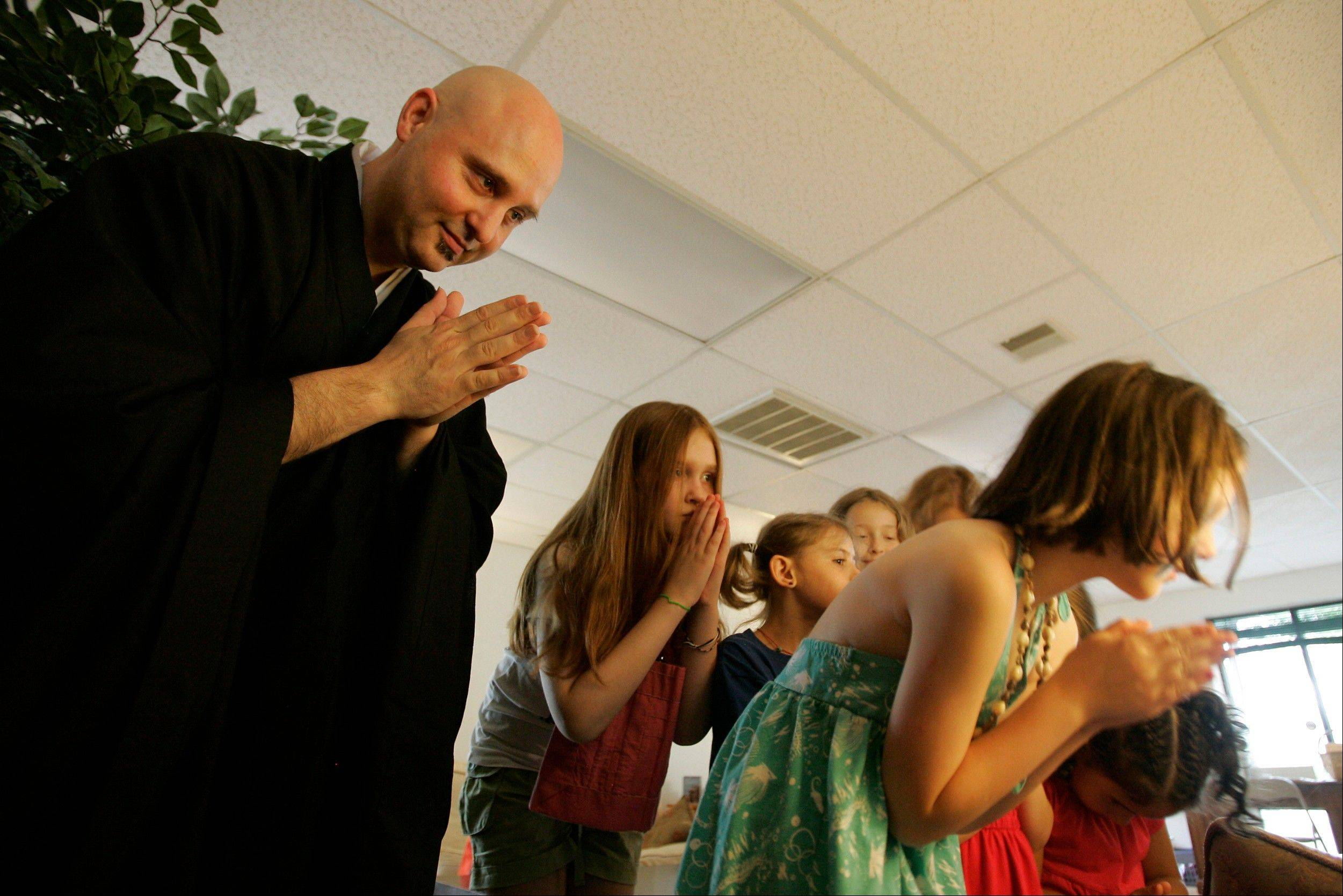 Rev. Jay Rinsen Weik bows with children after lighting an incense candle at the Toledo Zen Center in Holland, Ohio. The center has created a Sunday school and other programs to be especially welcoming to families.